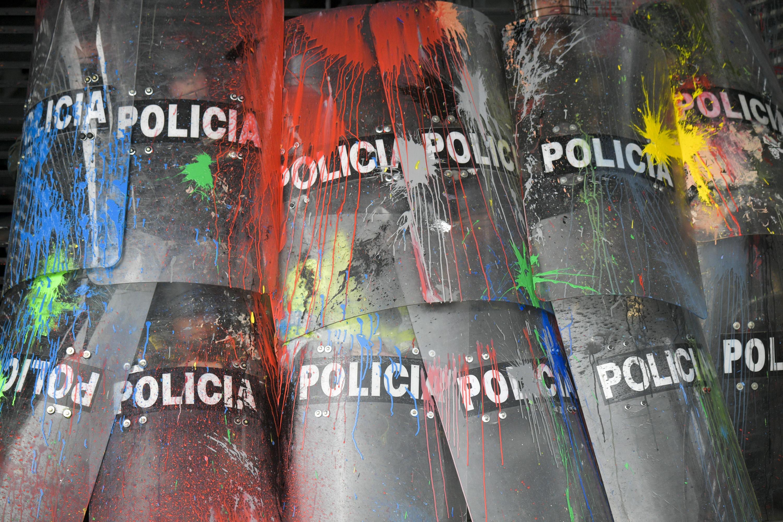 Полицейские прикрываются щитами во время столкновений со студентами, которые вышли намитинг заулучшение финансирования образования вБоготе. 10 октября 2019 года.