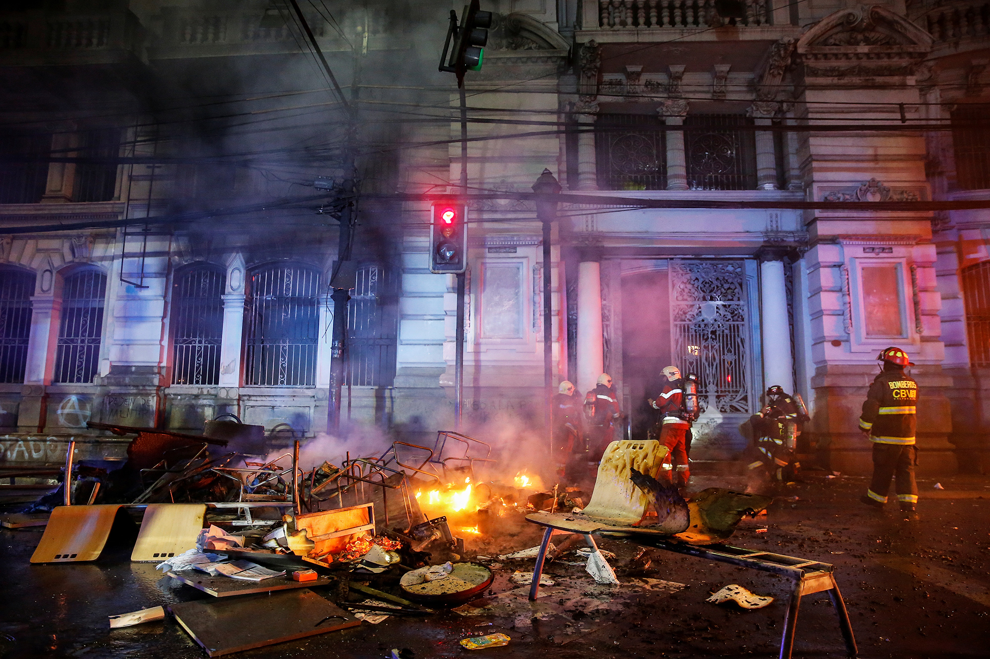 Firemen work near burnt furniture and objects outside the building of Chilean newspaper El Mercurio de Valparaiso during a protest against the government in Valparaiso, Chile