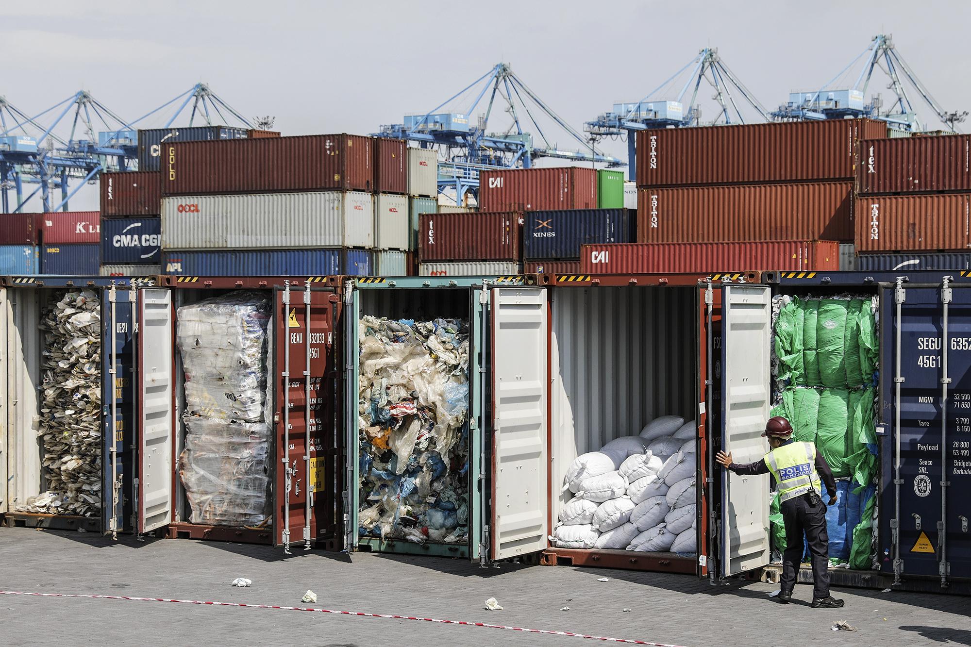 Помощник полицейского проверяет пластиковые отходы вгрузовых контейнерах, прежде чем отправить их туда, откуда они прибыли. Местный политик Ё Би Инь накануне заявила, что Малайзия отправит 450 метрических тонн загрязненных пластиковых отходов обратно встраны происхождения. Отходы поступили изАвстралии, США, Канады, Саудовской Аравии, Японии, Китая, Испании иБангладеш. Порт-Кланге, Селангор, Малайзия, 28 мая 2019 года.
