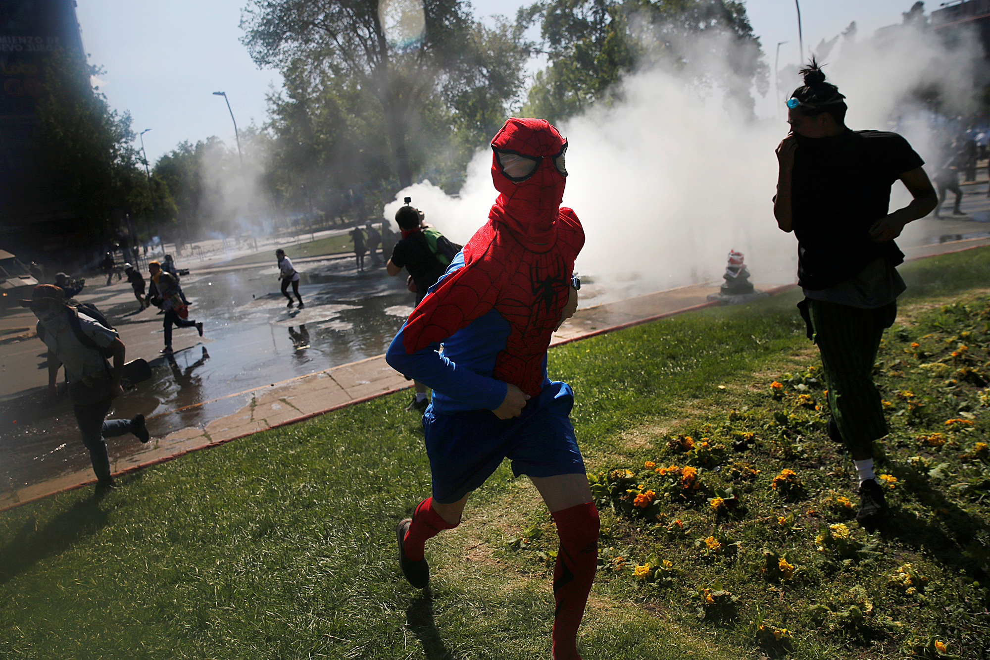 A demonstrator dressed as Spiderman runs from tear gas during a protest against Chile's state economic model in Santiago October 20, 2019.