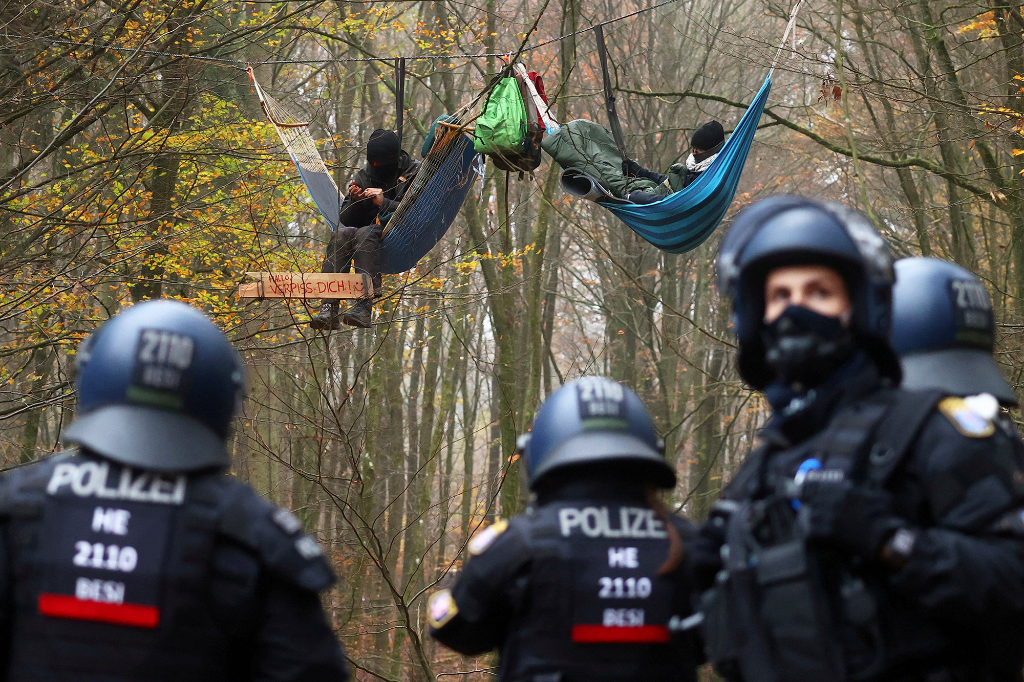 Police officers are seen as demonstrators lie in hammocks hanging from trees during a protest against the extension of the A49 motorway, in a forest near Stadtallendorf, Germany, November 11, 2020. REUTERS/Kai Pfaffenbach