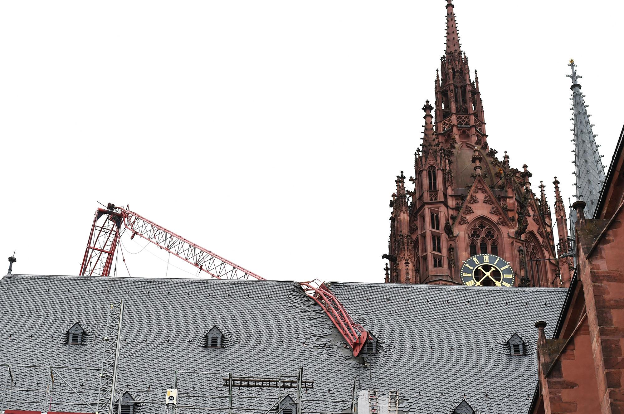 Стрела строительного крана, снесенного ураганным ветром, прогнулась иупала накрышу Франкфуртского собора, Германия.