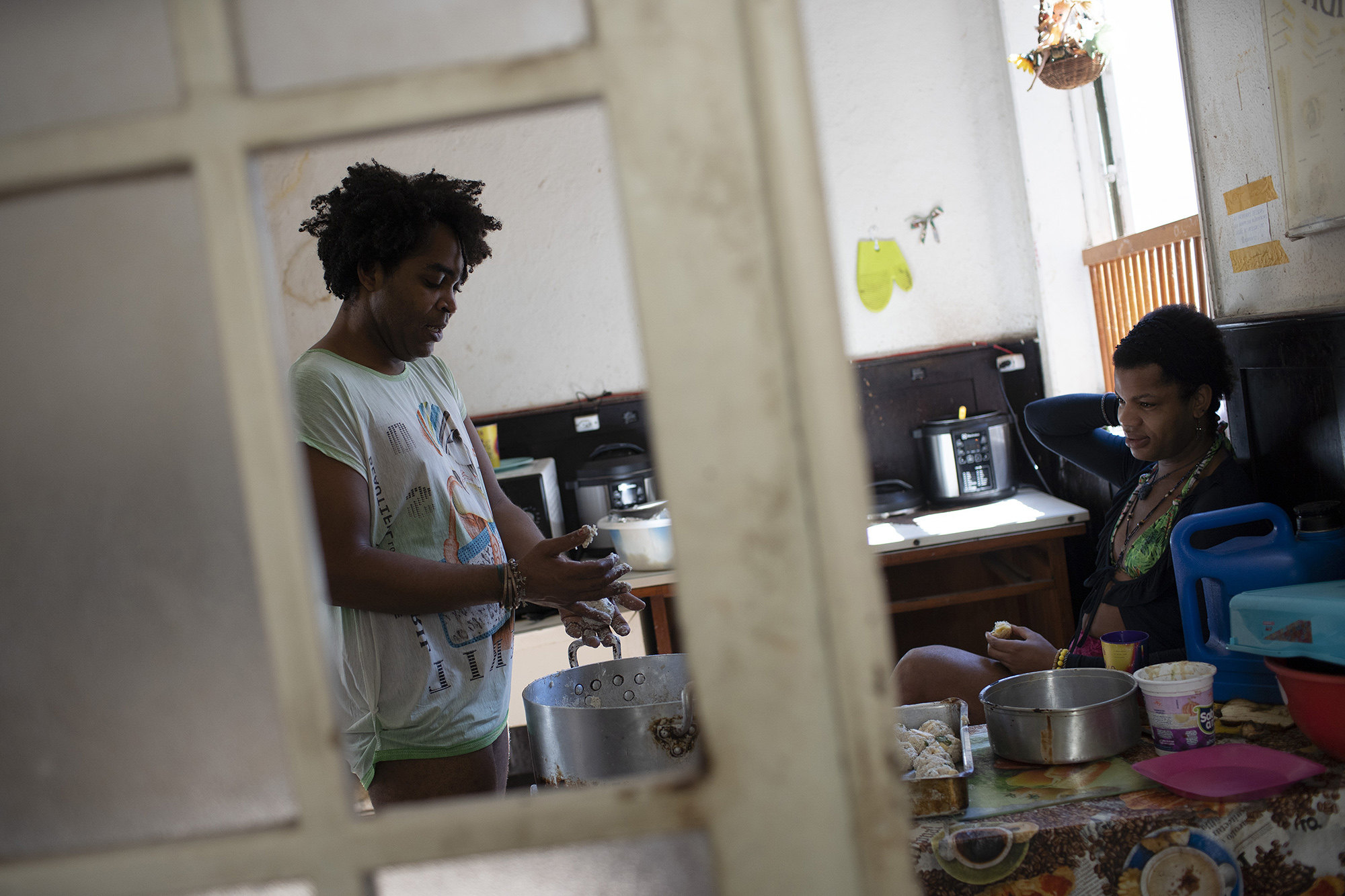 Morgana keeps Micaela company as she prepares rice balls for lunch in the kitchen of the squat known as Casa Nem, occupied by members of the LGBTQ community who are in self-quarantine as a protective measure against the new coronavirus, in Rio de Janeiro, Brazil, Wednesday, July 8, 2020. Self-imposed lockdown is one of few ways this traditionally marginalized group has found to minimize COVID-19 risks, while others remain vulnerable on the streets.