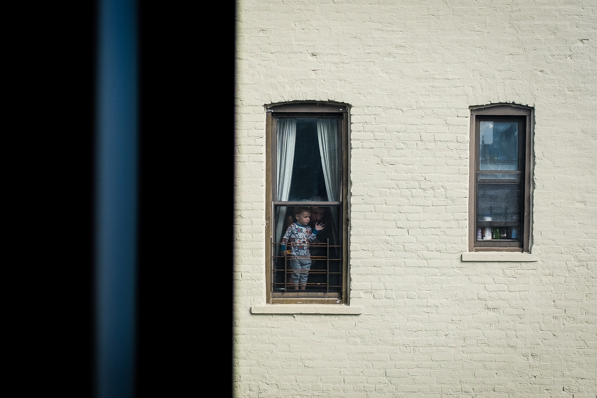 A little boy and his father can be seen looking out of a window in Brooklyn, New York, USA, 16 March 2020. New York City Public schools will close due to coronavirus until at least 20 April. EPA-EFE/Alba Vigaray