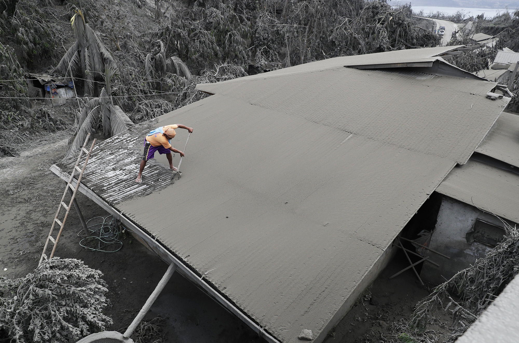 A resident clears volcanic ash from his roof in Laurel, Batangas province, southern Philippines on Tuesday, Jan. 14, 2020. Taal volcano is spewing ash half a mile high and trembling with earthquakes constantly as thousands of people flee villages darkened and blanketed by heavy ash. (AP Photo/Aaron Favila), APTOPIX