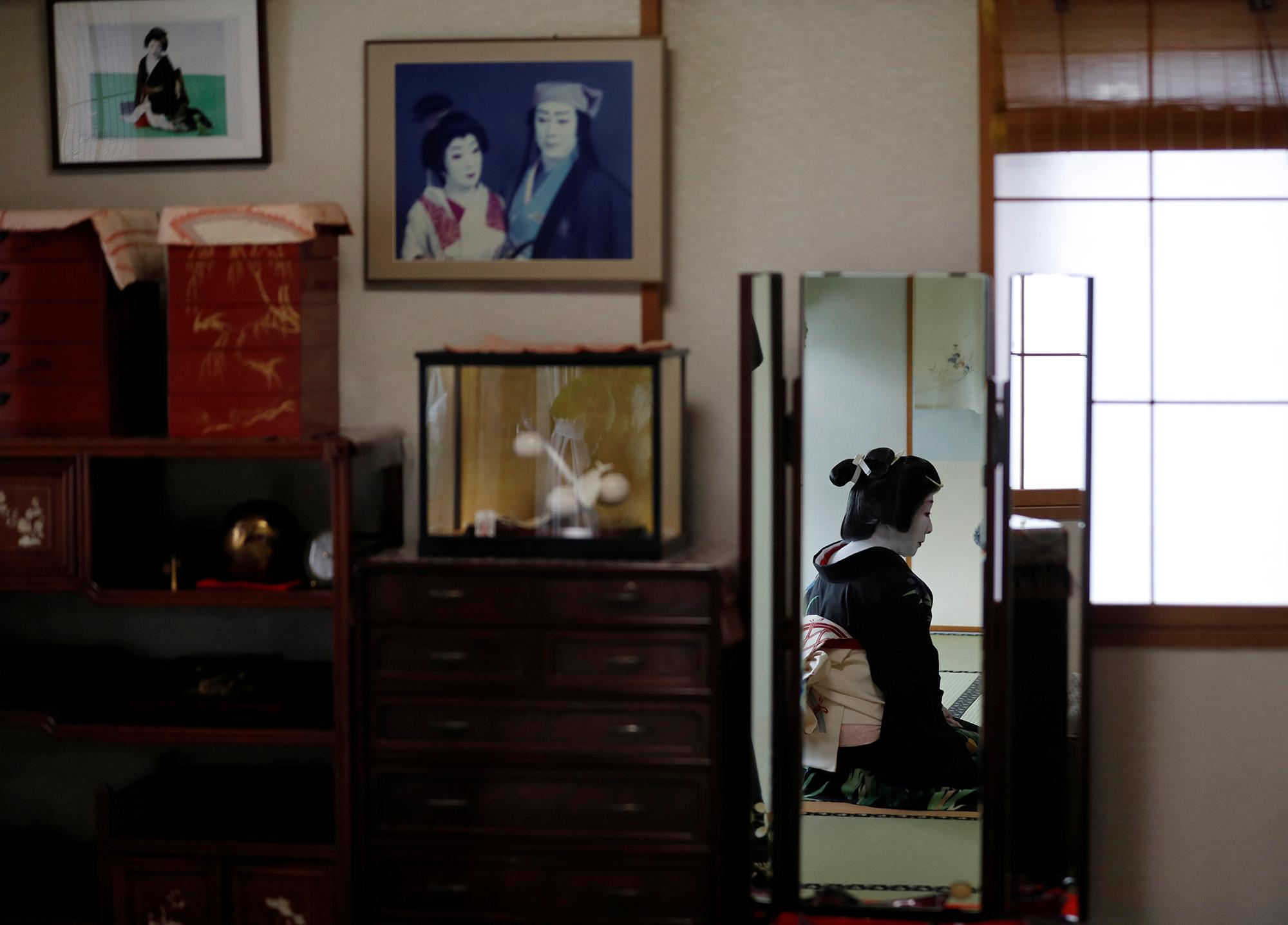 Гейши Икуко сидит передзеркалом всвоей гостиной.