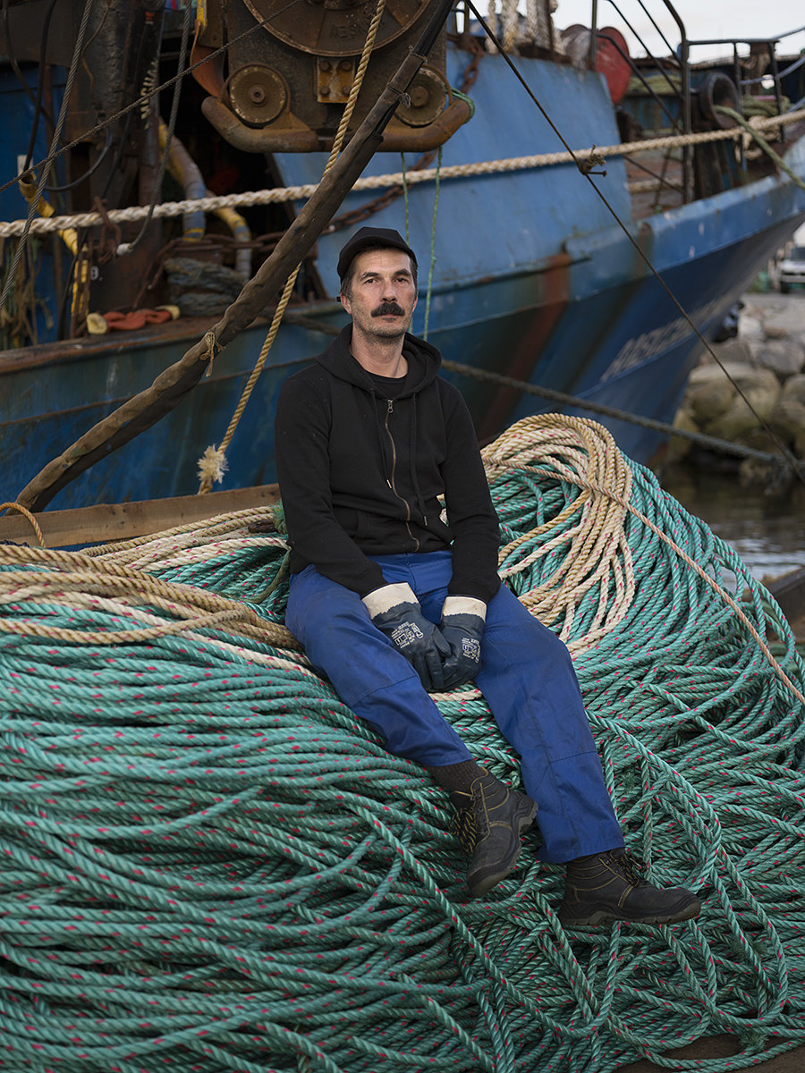 Sergey, Russian crab fisherman in front of his trawler moored at the port of Kirkenes, Norway.