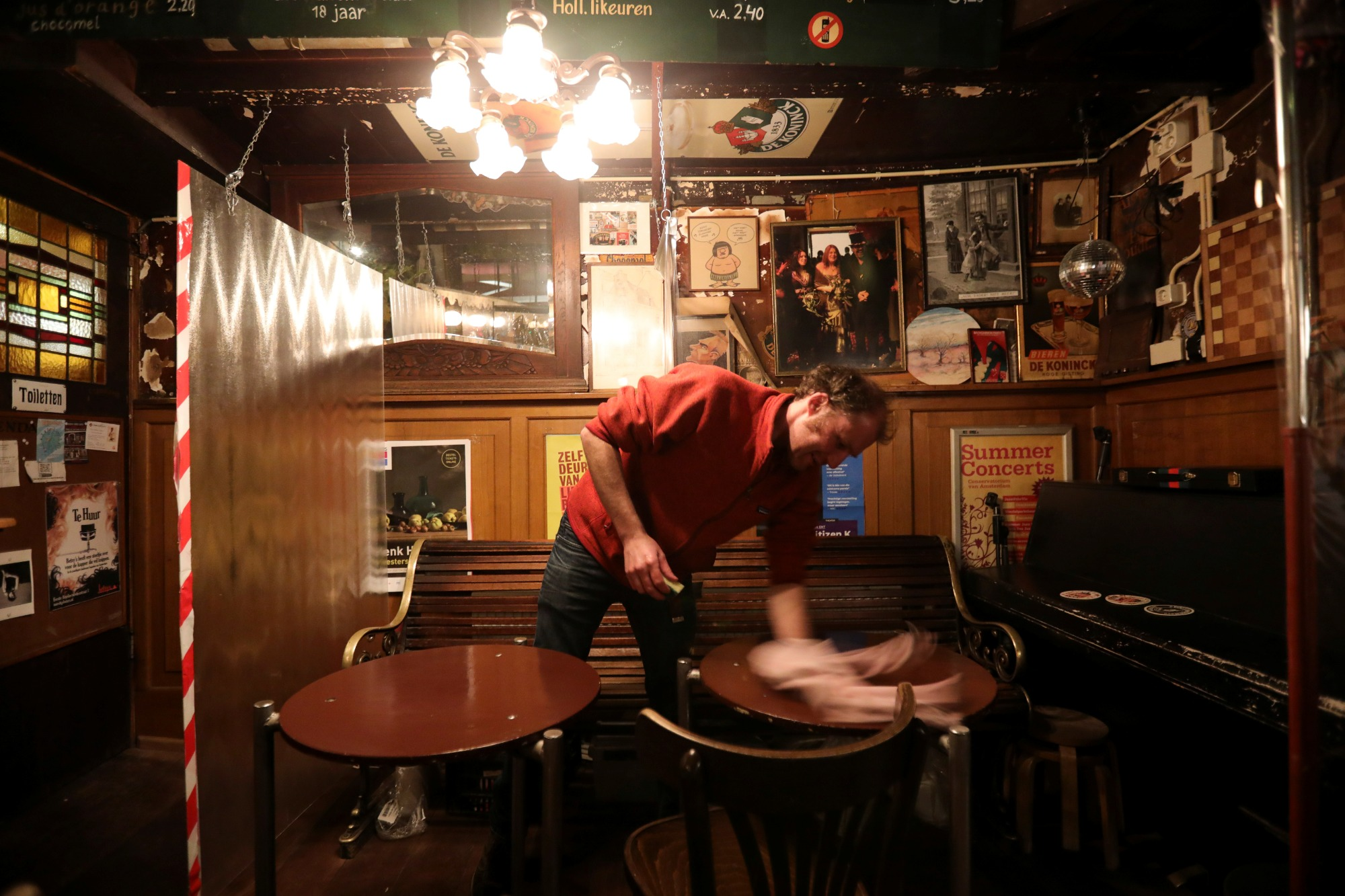 A man cleans a bar after it closed following the new restrictions announced by the Dutch government, as the Netherlands battle to control the spread of the coronavirus disease (COVID-19), in Amsterdam, Netherlands October 14, 2020. REUTERS/Eva Plevier