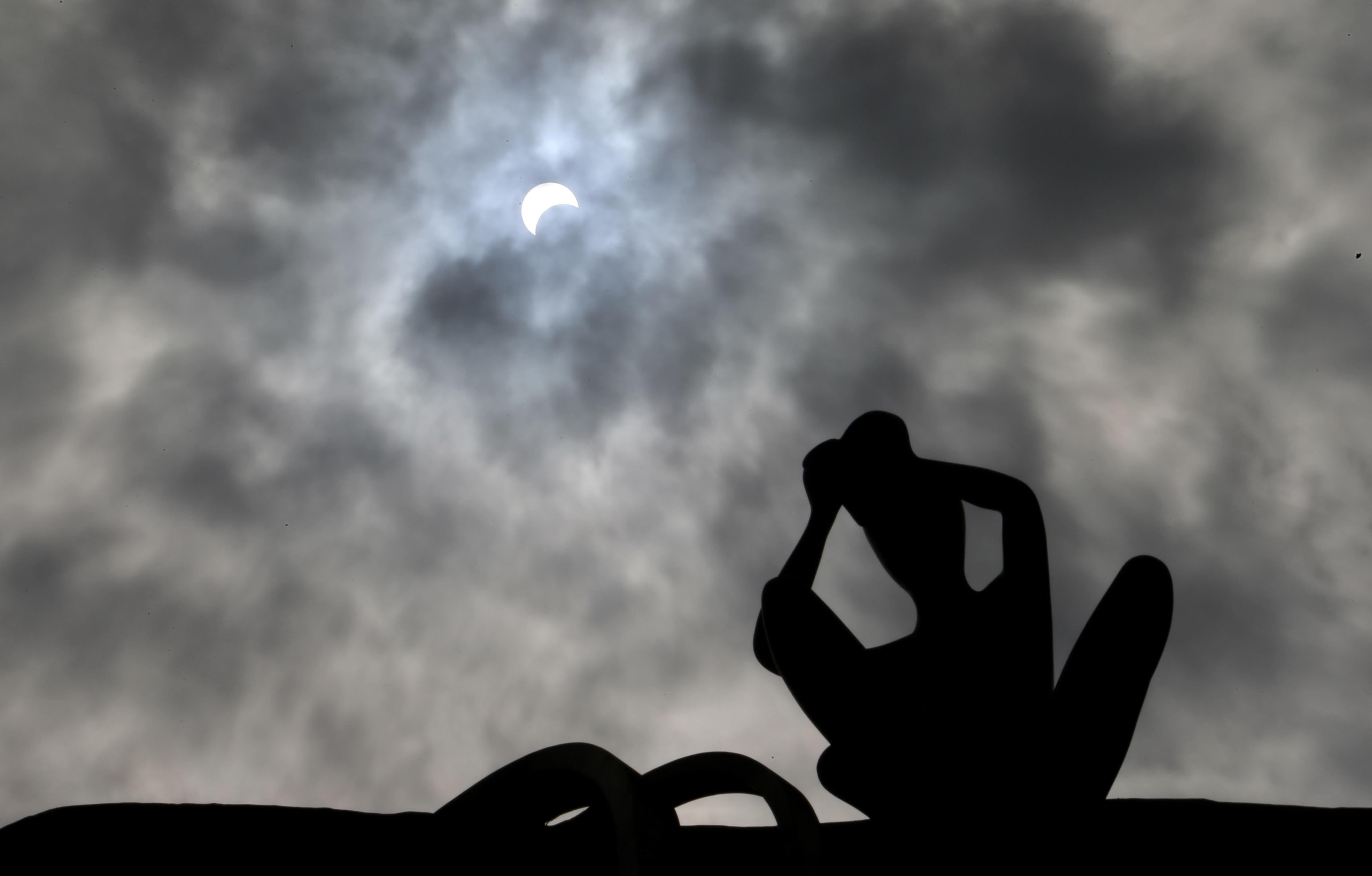 Жители китайского Куньмина наблюдают засолнечным затмением