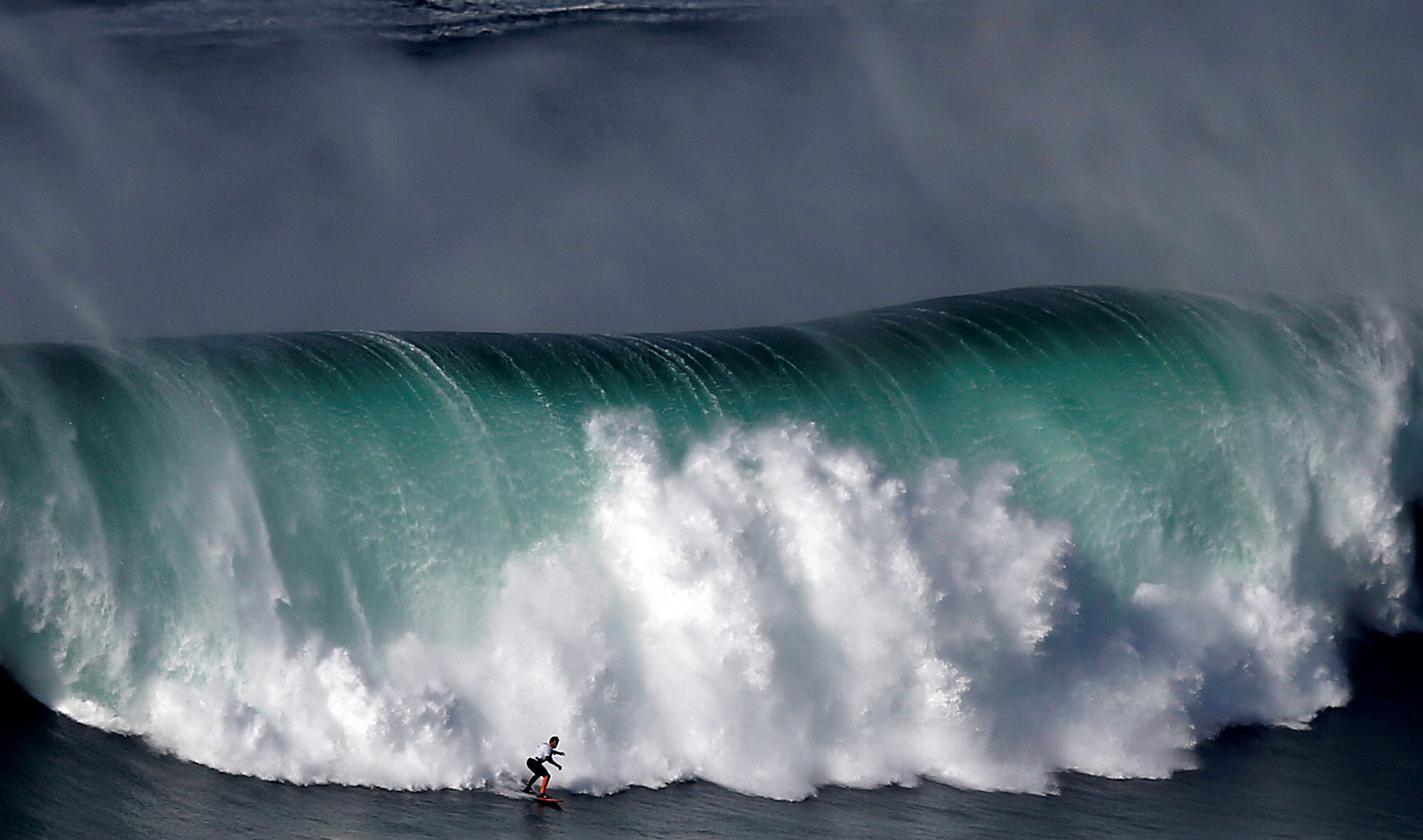 Серфер ловит волну вПрайа-ду-Норте, Португалия.