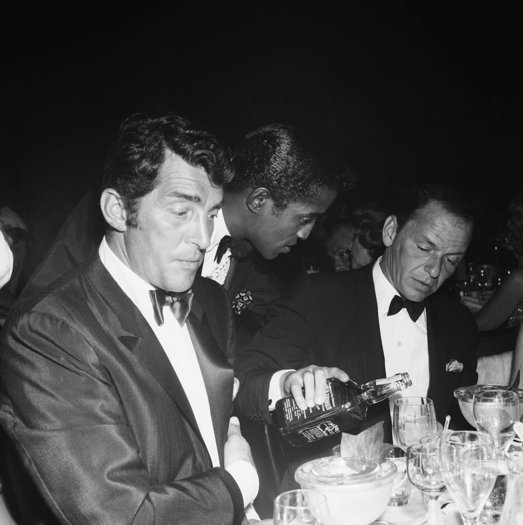 Singer Dean Martin and Sammy Davis, Jr. sit at a table as fellow singer and Rat Pack member Frank Sinatra pours Jack Daniels from a bottle at the Cocoanut Grove during Eddie Fisher's opening night on July 25, 1961 in Los Angeles, California. (Photo by Earl Leaf/Michael Ochs Archives/Getty Images)
