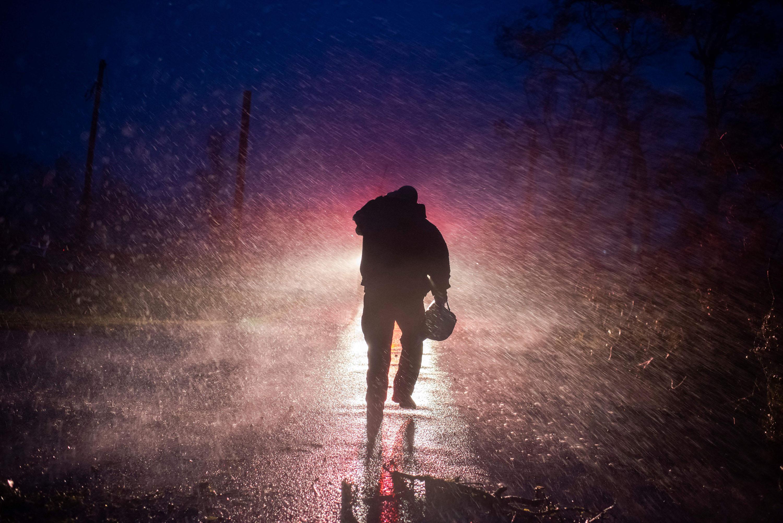 Начальник пожарной службы Монтегута Тоби Генри возвращается ксвоей пожарной машине поддождем, пока пожарные прорубают деревья надороге вБурге, штат Луизиана, 29 августа 2021 года.