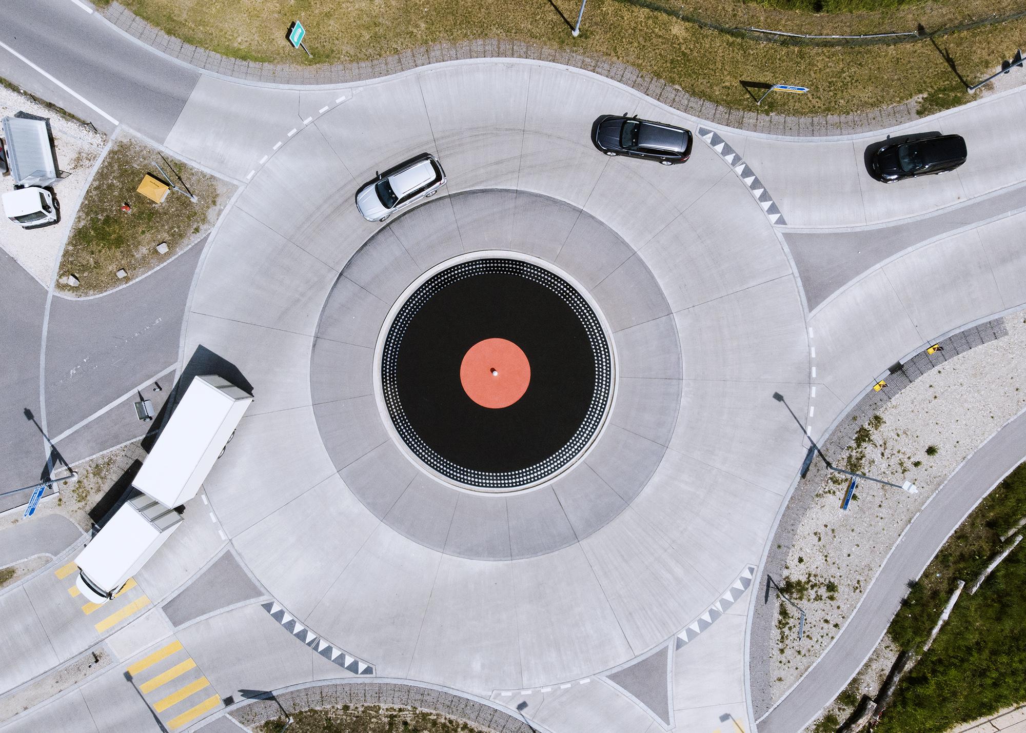 На фотографии, сделанной спомощью дрона, изображены автомобили, движущиеся наперекрестке скруговым движением ввиде огромной виниловой пластинки. 27 мая 2019 года, Лиссе, Швейцария.