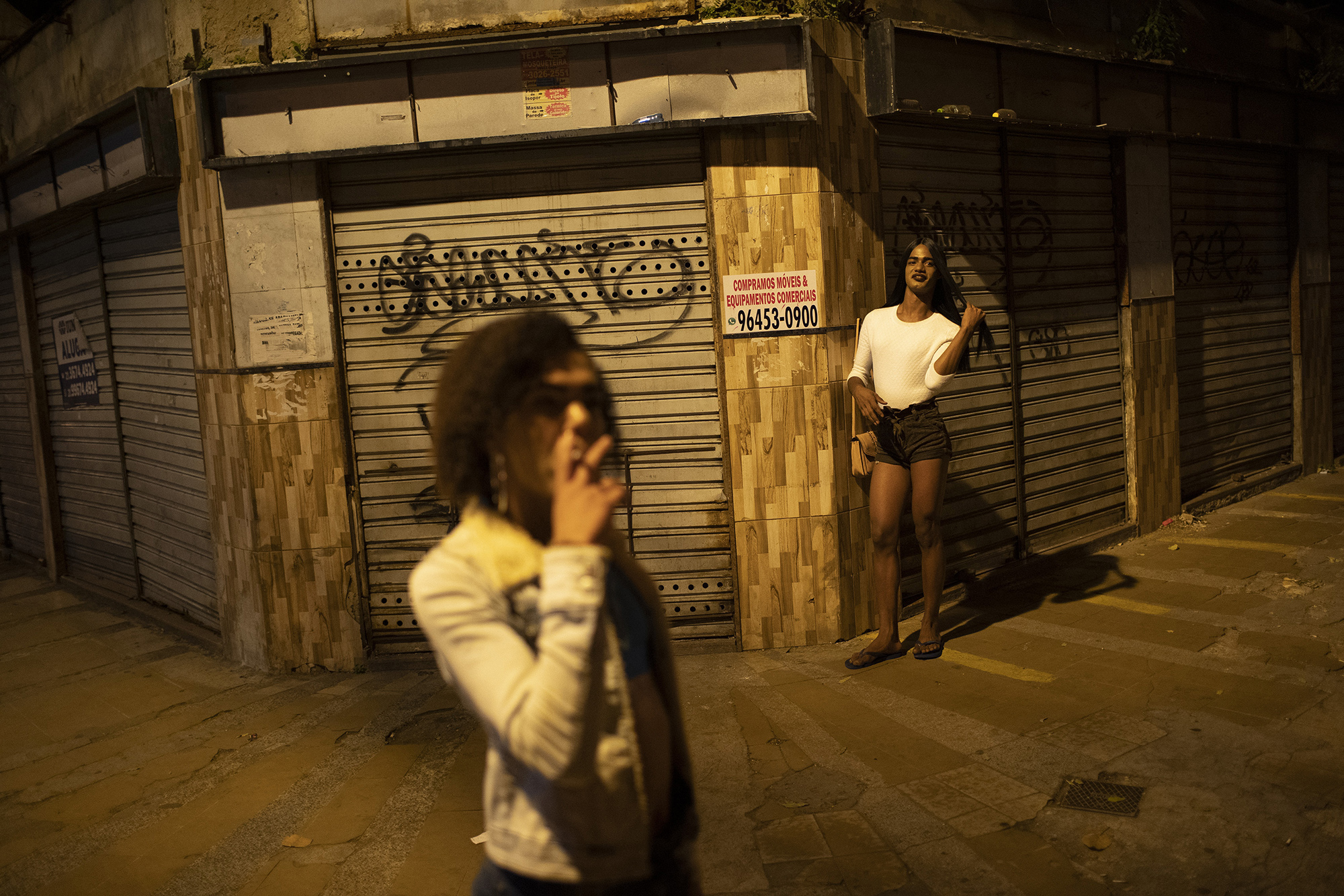 "Transgender sex worker Alice Larubia smokes a cigarette as she waits for customers in Niteroi, Brazil, Saturday, June 27, 2020, amid the new coronavirus pandemic. After a month quarantining at home with some financial support from family, Larubia resumed work in Niteroi, a city across the bay from Rio. ""Necessity spoke louder (than the pandemic) and I had to come back to the street,"" Larubia said while waiting for clients with a small group of colleagues."