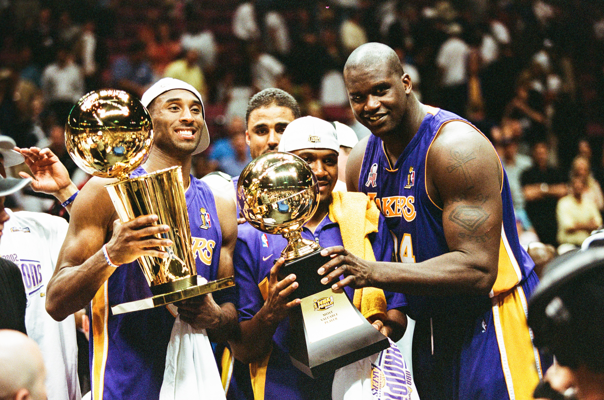 EAST RUTHERFORD, NJ - JUNE 12: Kobe Bryant, Lindsey Hunter and Shaquille O'Neal of the Los Angeles Lakers celebrate following Game Four of the NBA Finals against the New Jersey Nets on June 12, 2002 at Continental Airlines Arena in East Rutherford, New Jersey. (Photo by Sporting News via Getty Images via Getty Images)