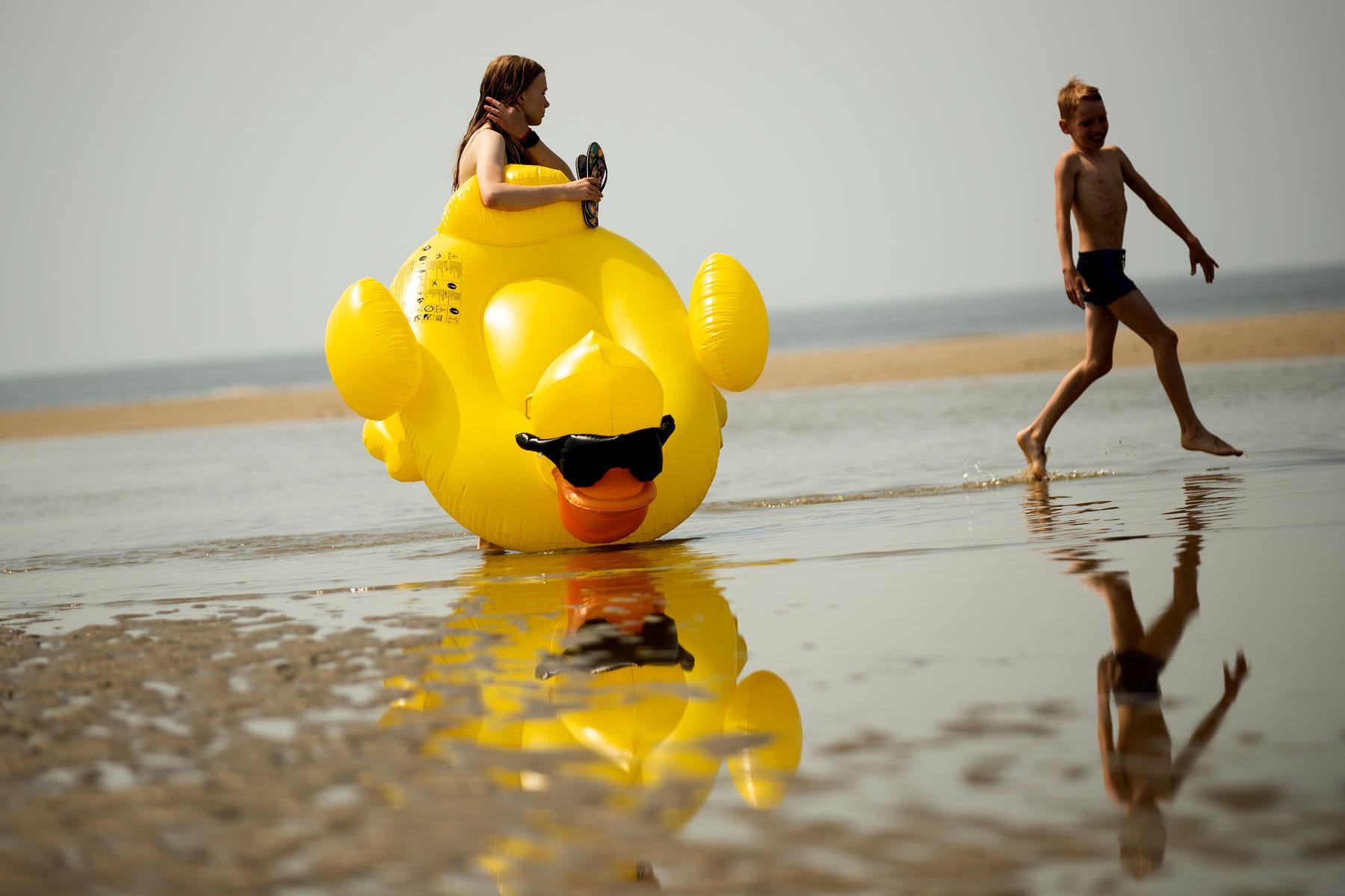 Дети играют напляже вжаркий день вДе Хаан, Бельгия.