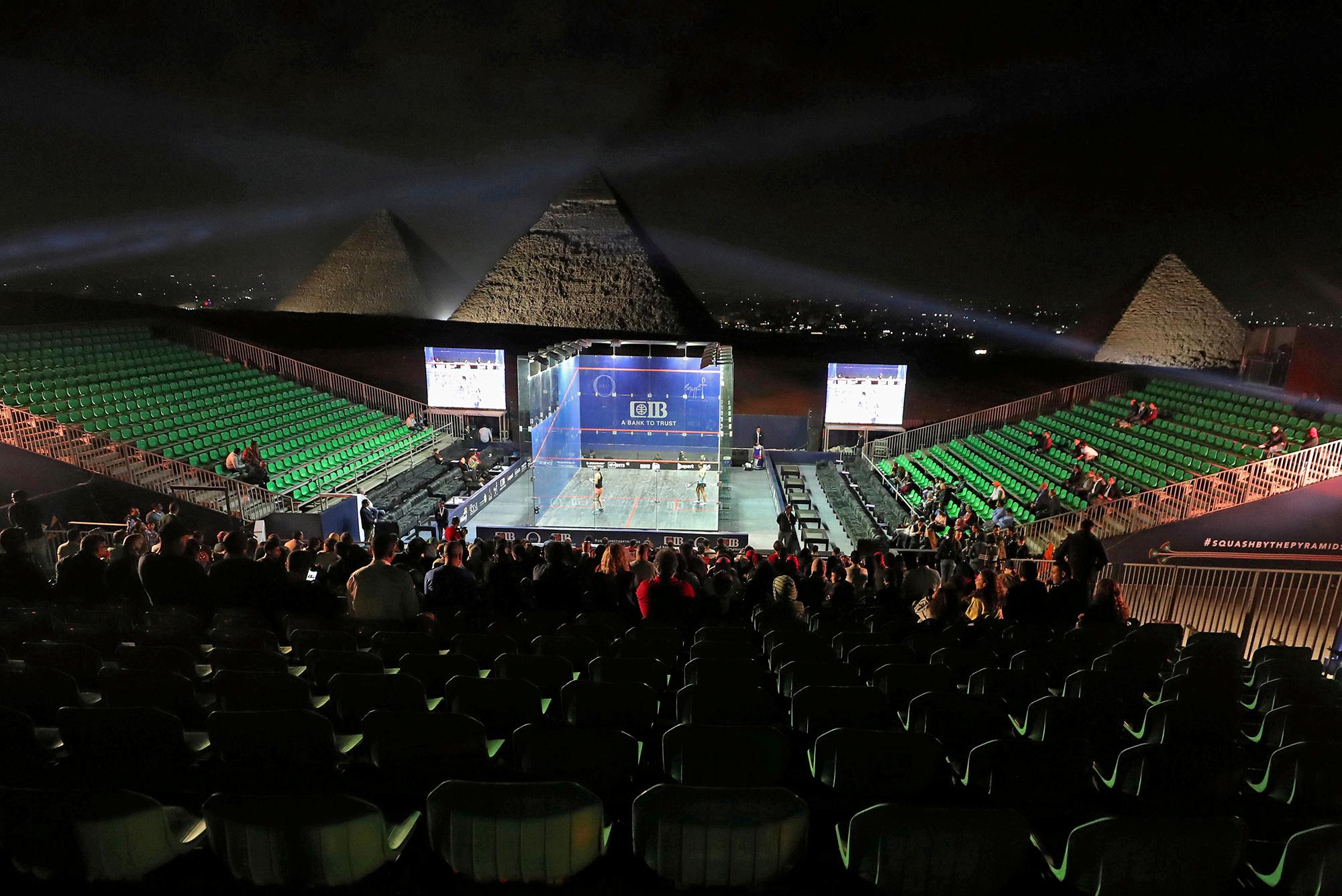 Люди смотрят матч посквошу передна фоне пирамид вГизе. Матч проходил врамках Чемпионата мира пофутболу среди женщин. 26 октября 2019