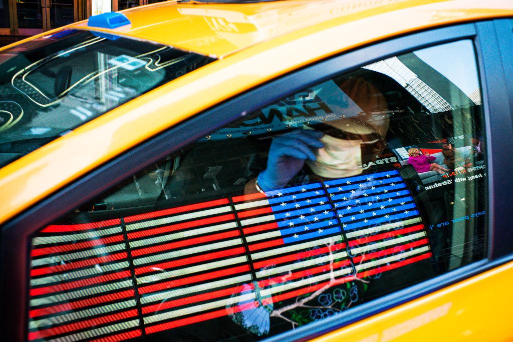 Водитель такси взащитной маске проезжает поТаймс-Сквер, Нью-Йорк, 26 марта 2020