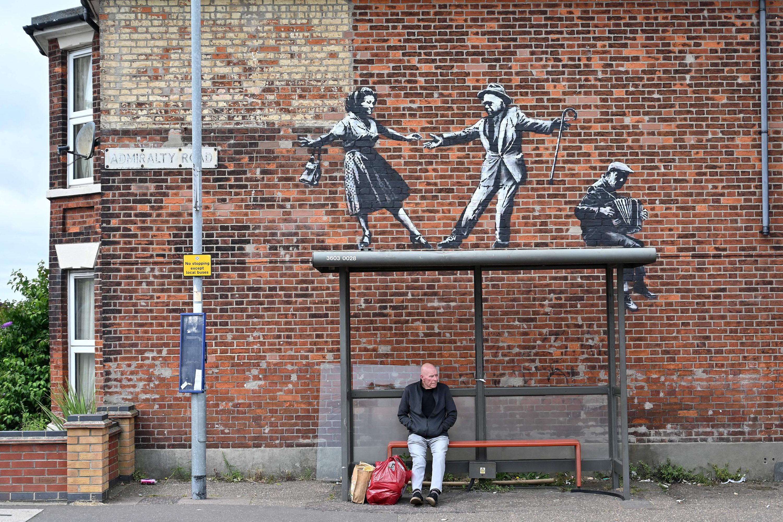 Мужчина ждет автобус наостановке подновым граффити Бэнкси вгороде Грейт-Ярмуте навосточном побережье Англии, 8 августа 2021 года.