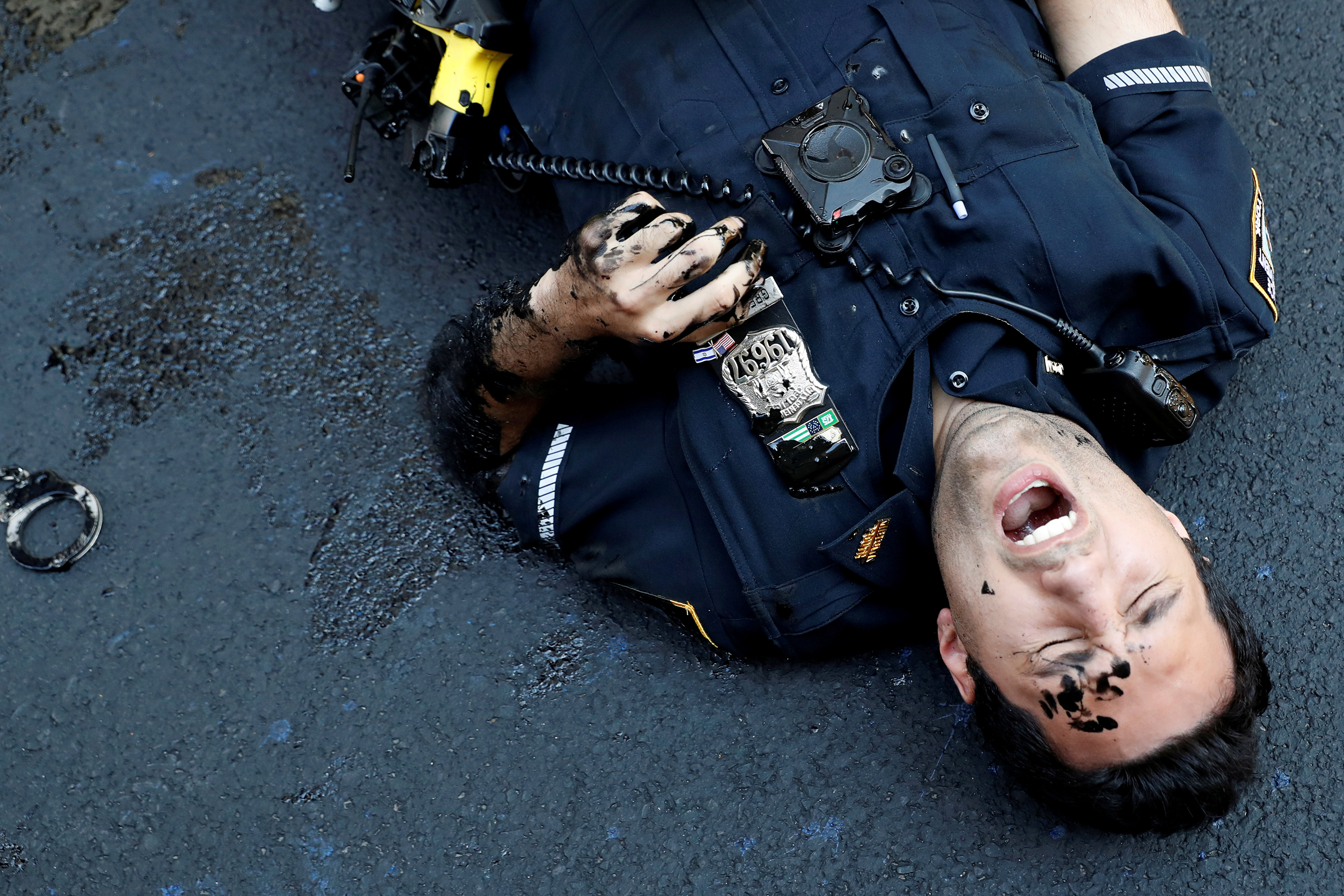 An officer from the New York Police Department is seen injured after attempting to detain a protester smearing paint on the Black Lives Matter mural outside of Trump Tower on Fifth Avenue in Manhattan, New York City, U.S., July 18, 2020