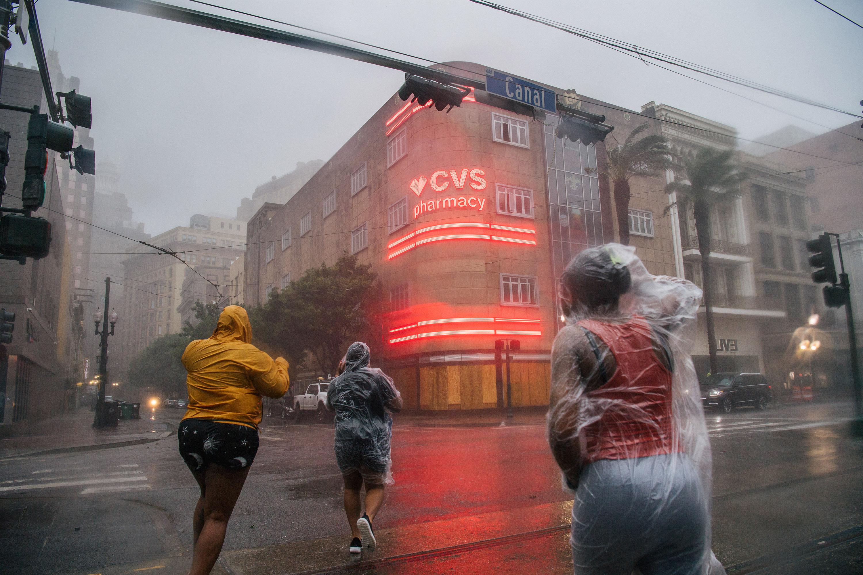 Жители Нового Орлеана переходят дорогу во время урагана