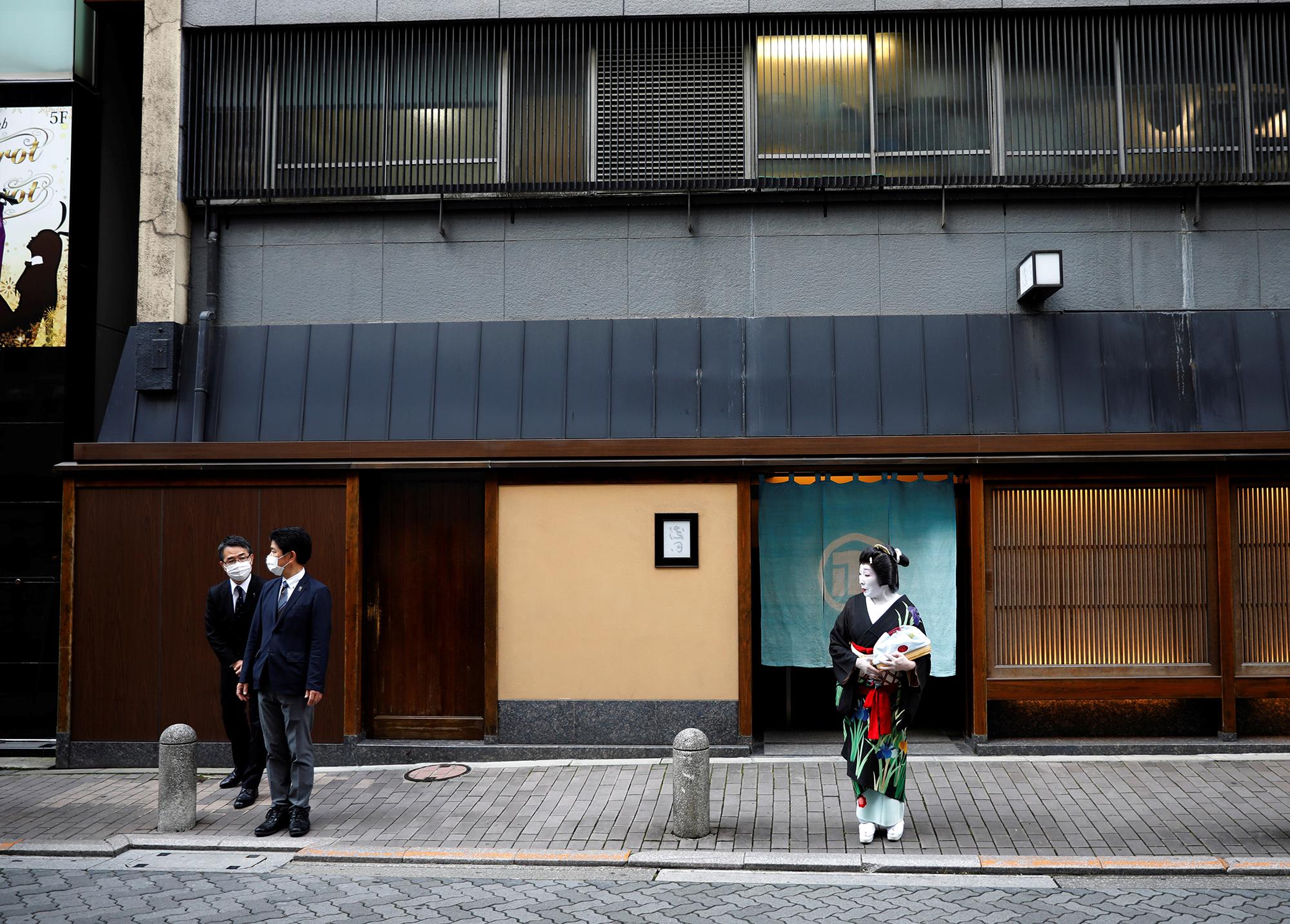 Сотрудники ресторана Asada взащитных масках стоят наулице сгейшей Икуко вожидании ее коллеги.