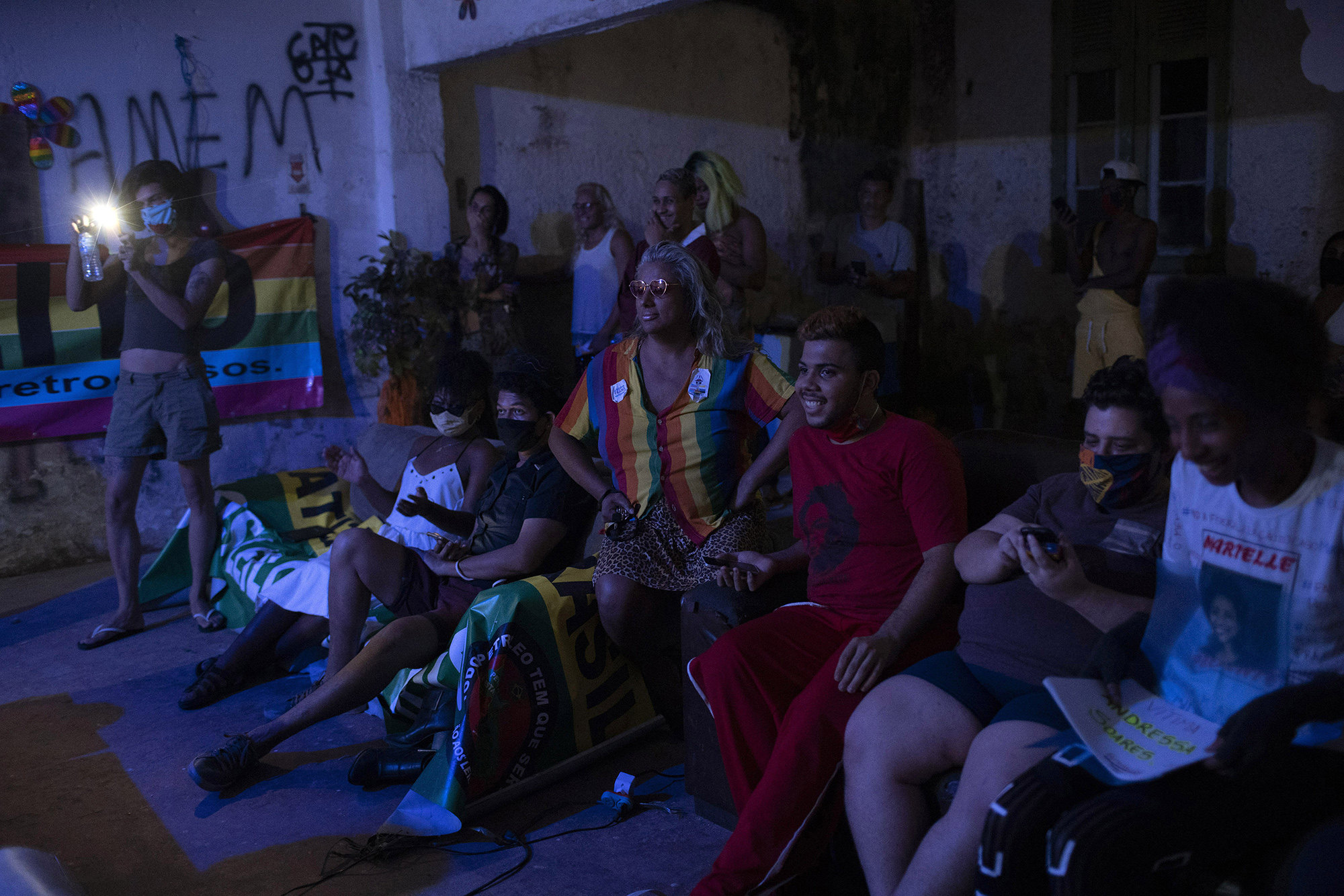 Indianara Siqueira, wearing a rainbow colored shirt, sits with fellow residents to watch their weekly presentations performed on a makeshift stage at the squat known as Casa Nem, occupied by members of the LGBTQ community who are in self-quarantine as a protective measure against the new coronavirus, in Rio de Janeiro, Brazil, Saturday, May 23, 2020. Siqueira, 49, a transgender sex worker and activist leads Casa Nem.