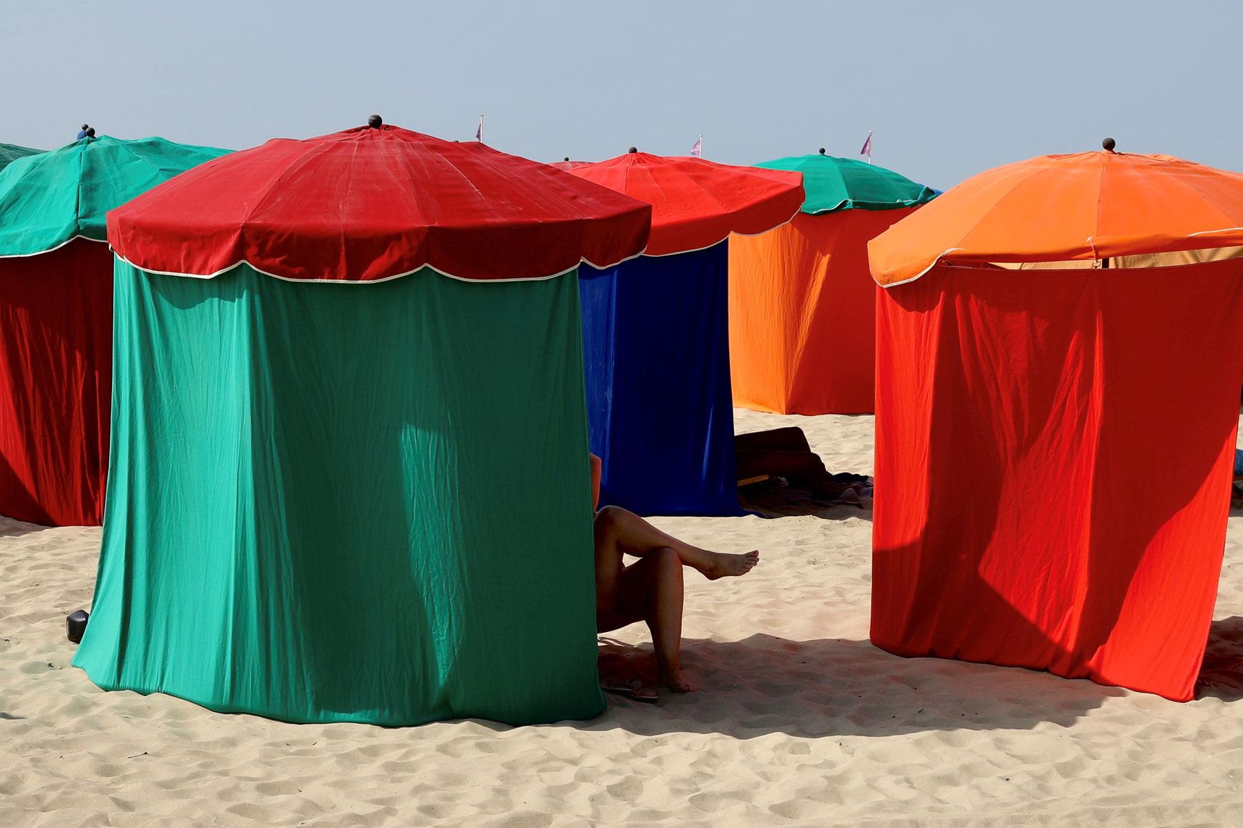 Женщина отдыхает подтентом напляже вДовиле.