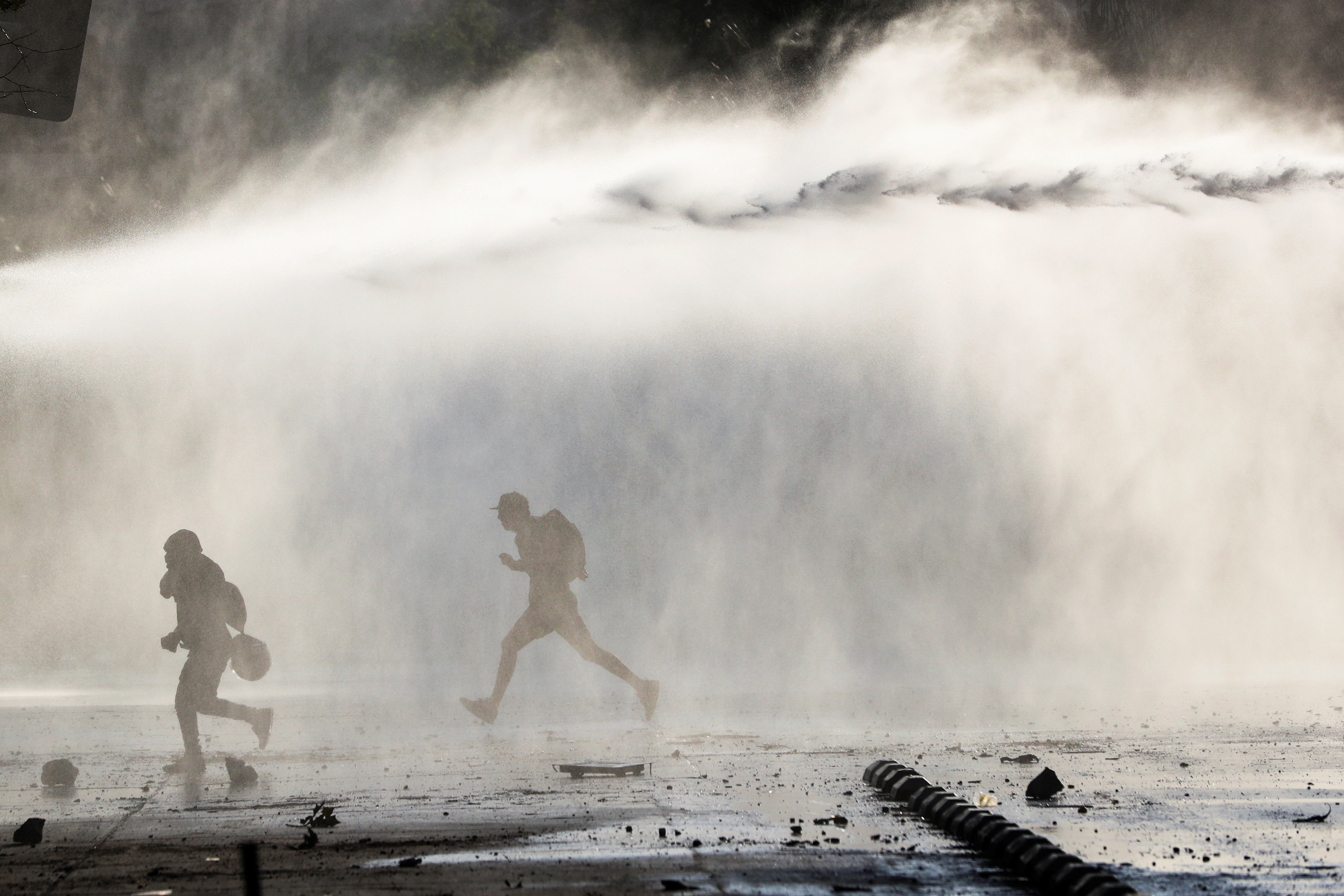 DATE IMPORRTED:October 19, 2019Demonstrators run from the police water cannon during a protest against the increase in subway ticket prices in Santiago, Chile, October 19, 2019