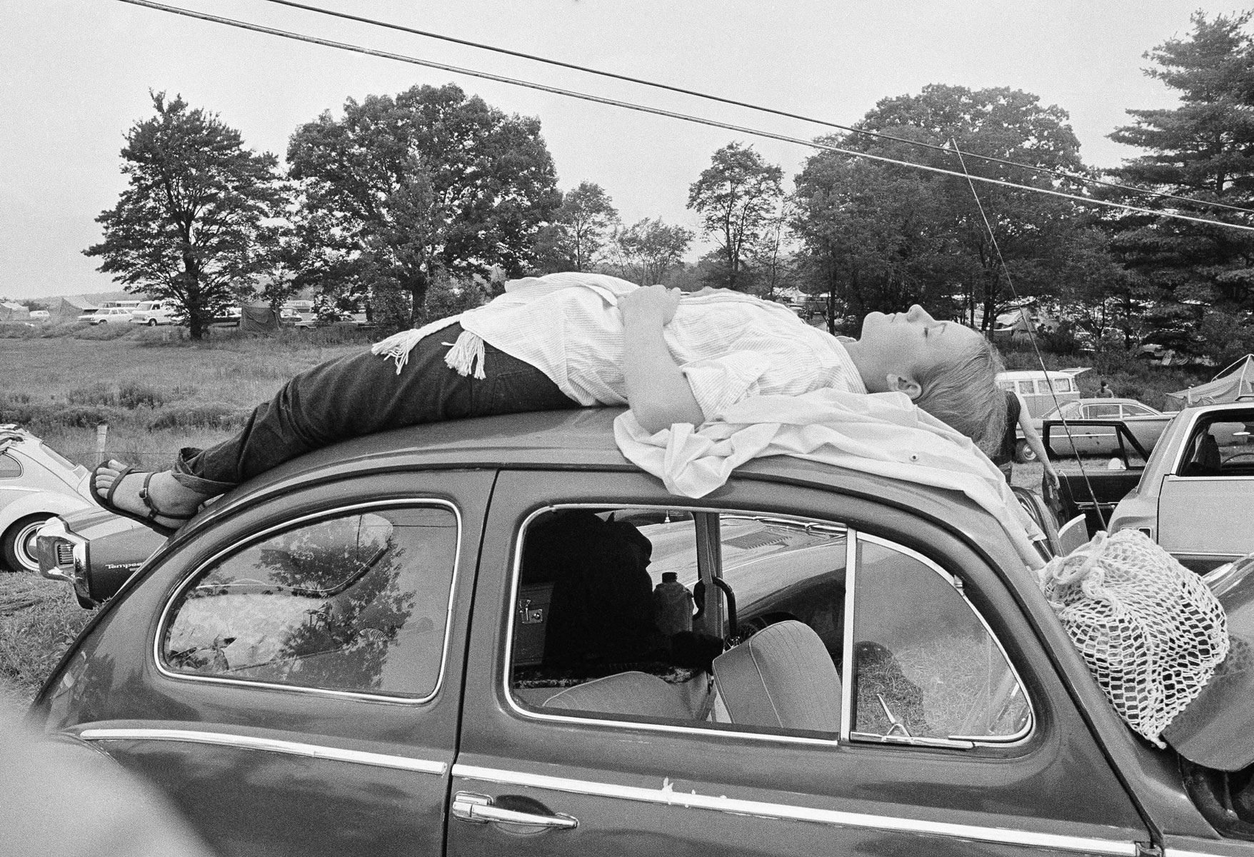 Aug. 16, 1969 file photo, a young woman naps on top of her car while trying to reach the Woodstock Music and Art Festival in Bethel, N.Y. Organizers had sold 186,000 tickets; ultimately an estimated 400,000 people showed up for the festival on a 600-acre parcel of farmland. (Фото: AP/East News)