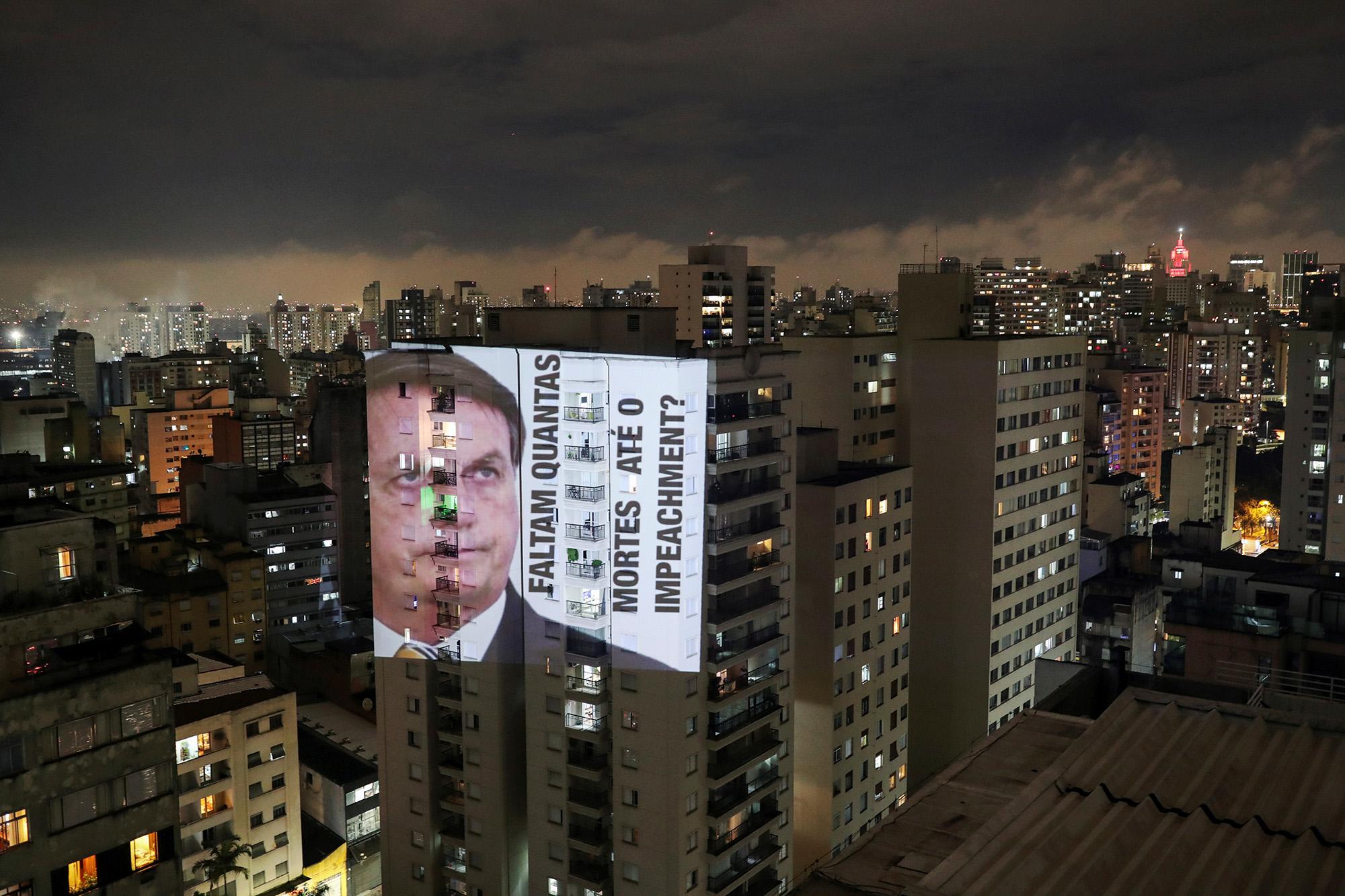 Фото президента Бразилии Жаира Болсонару сподписью «Сколько смертей доимпичмента?», спроецированное наздание во время протеста против его политики вотношении коронавируса икризиса здравоохранения, Сан-Паулу , Бразилия, 15 января 2021 г.