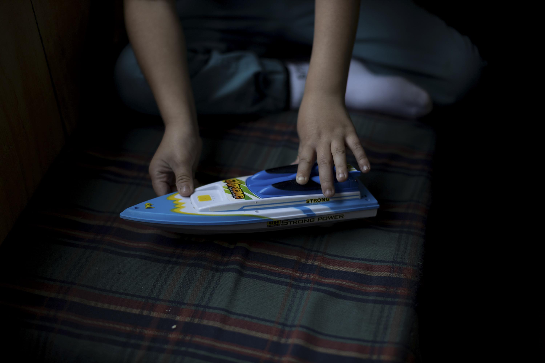 Семилетний Диего Герреро играет со своей игрушечной лодкой накухне своего дома вдеревне Сотомо, недалеко отгорода Кочамо, регион Лос-Лагос, Чили, 6 августа 2021 года.