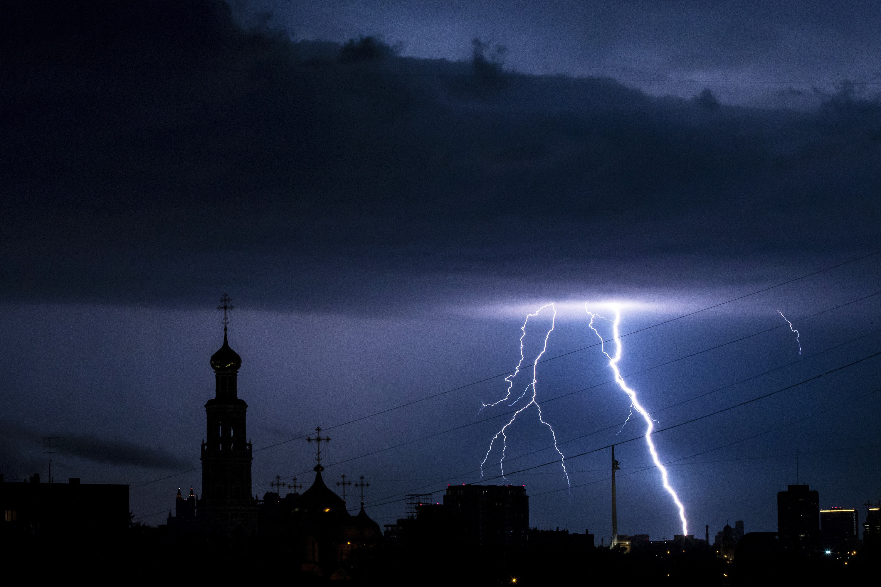 Lightning strikes over the Poklonnaya Hill, and lights the Novodevichy Convent, left, in Moscow, Russia, late Tuesday, July 7, 2020. The hot weather in Moscow is continuing, with temperatures forecast to reach over 30 degrees Celsius (86 Fahrenheit). (AP Photo/)