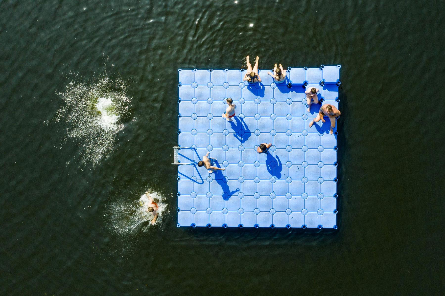 Люди отдыхают наплавающем понтоне наозере Альтвармбюхенер вГанновере, Германия.