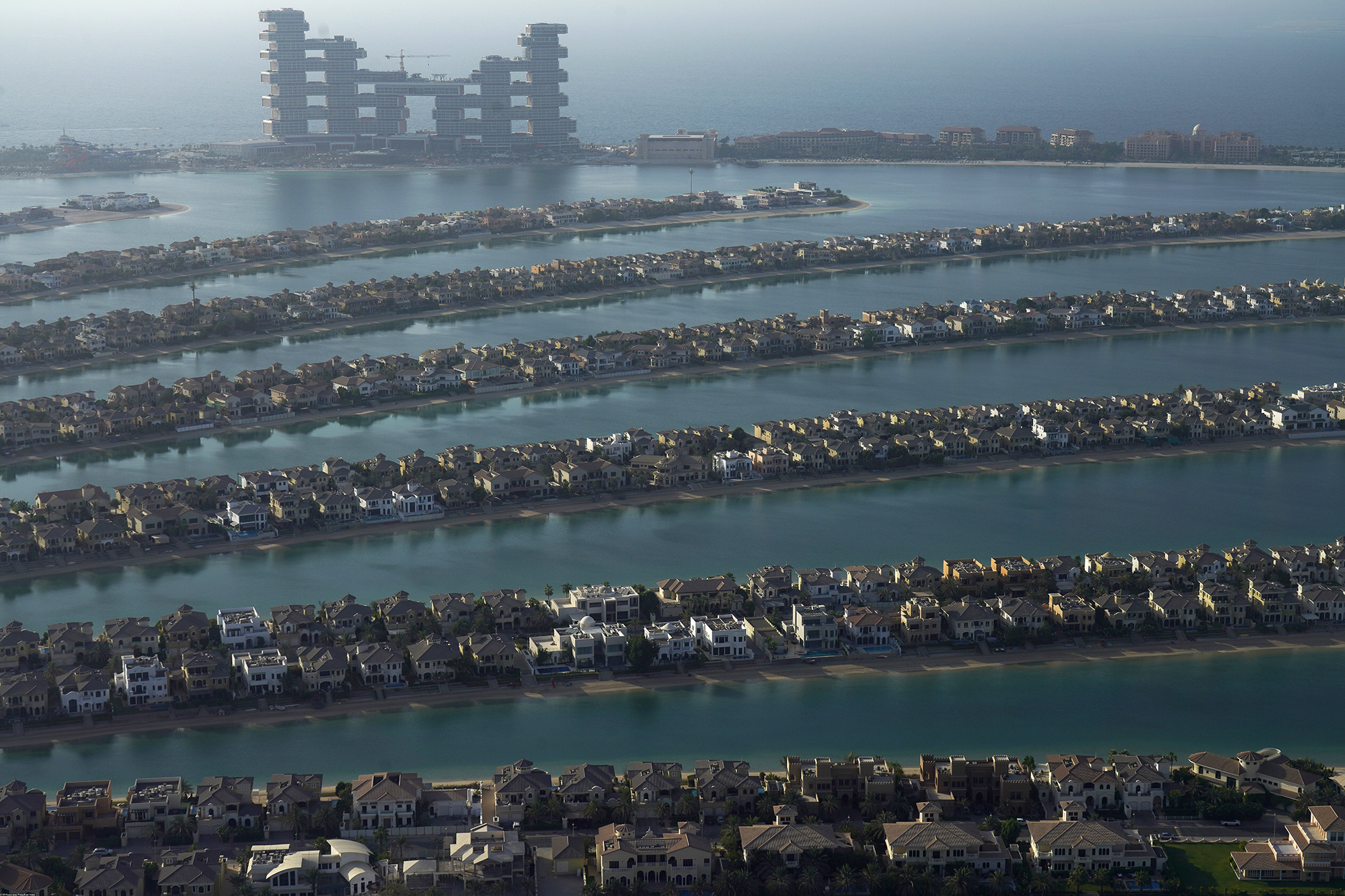 The fronds of the manmade Palm Jumeirah archipelago stretch out across the Persian Gulf with The Royal Atlantis Resort & Residences looming in the background in Dubai, United Arab Emirates, Monday, July 19, 2021.