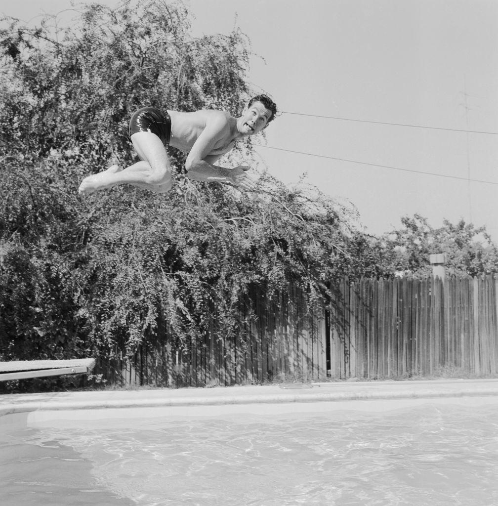 Джонни Карсон, ведущий «Шоу Джонни Карсона наCBS», прыгает вбассейн своего дома вЛос-Анджелесе, штат Калифорния, 5 июля 1956 года