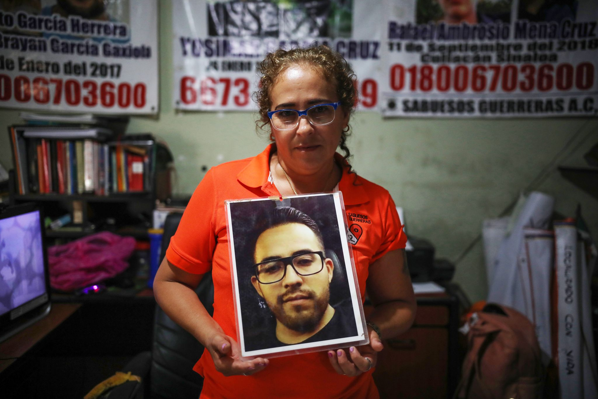 Maria Isabel Cruz Bernal, founder of Sabuesos Guerros, holds up a photo of her son, Yosimar Garcia, who has been missing for several years.