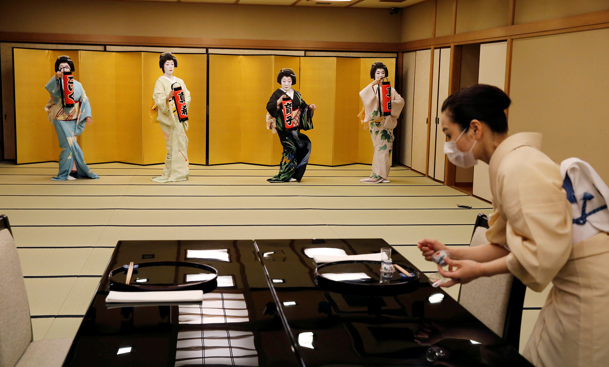 Гейши Коику, Маки, Икуко иМаю исполняют танец длякорреспондента Reuters.