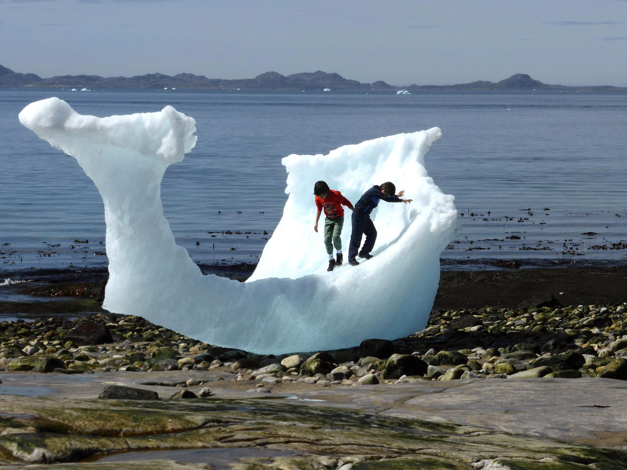 Дети играют среди айсбергов напляже вНууке, Гренландия, 5 июня 2016 г.