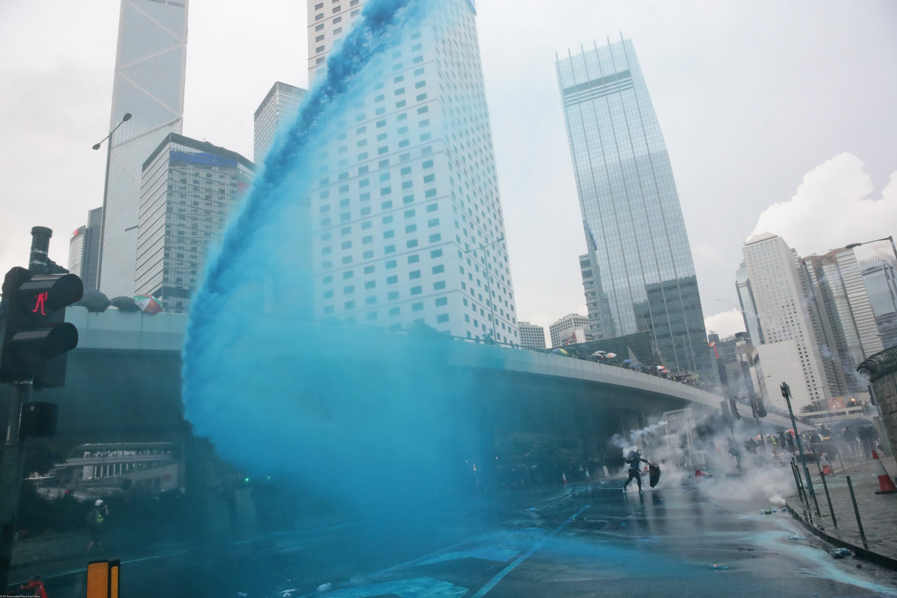 A protestor throws back an exploded tear gas shell, as police fire blue-colored water from water cannons in central Hong Kong, Saturday, Aug. 31, 2019. While other protesters marched back and forth elsewhere in the city, a large crowd wearing helmets and gas masks gathered outside the city government building. Some approached barriers that had been set up to keep protesters away and appeared to throw objects at the police on the other side. Others shone laser lights at the officers.