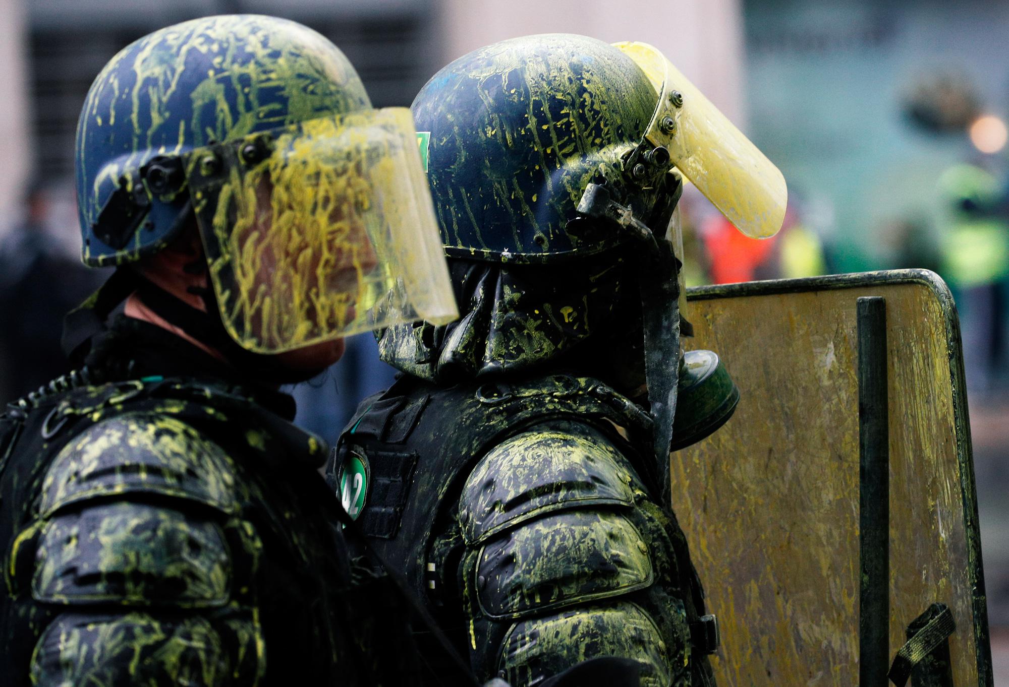 Облитые краской силовики во время демонстрации наЕлисейских полях