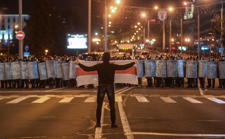 Демонстрант держит флаг передполицией, вооруженной дубинками ищитами, Минск, Беларусь