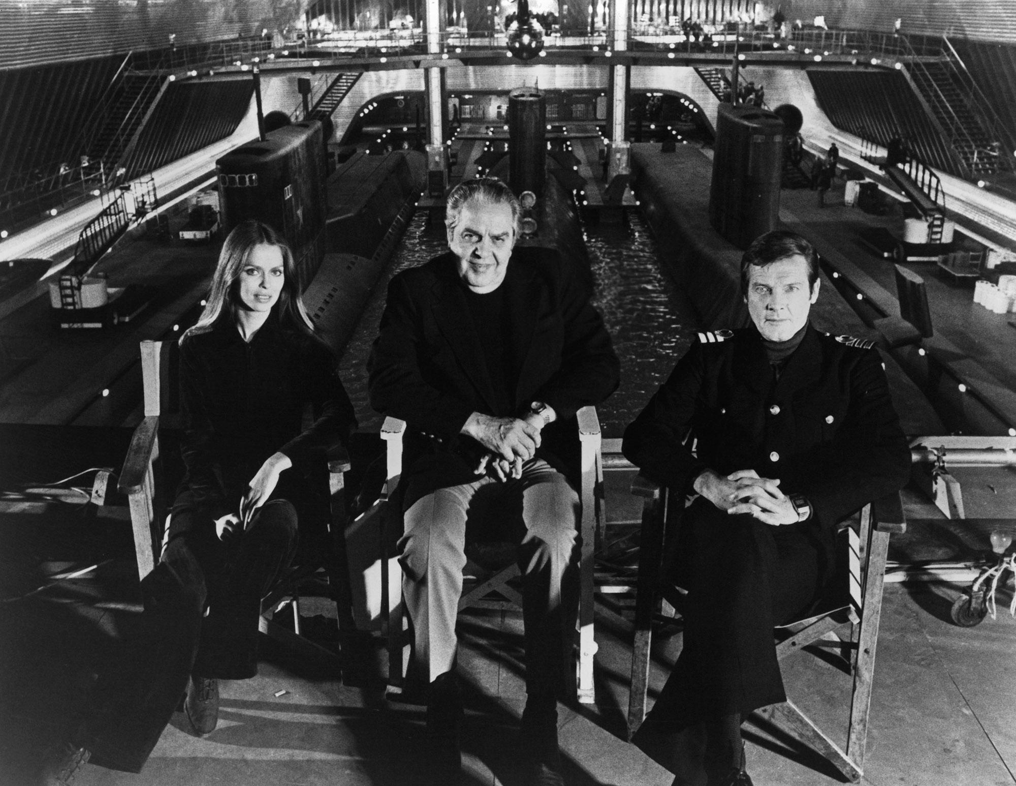 Актеры Барбара Бах иРоджер Мур сидят передподводным танком вPinewood Studios вместе спродюсером Альбертом Р. Брокколи во время создания фильма оДжеймсе Бонде «Шпион, который меня любил», 1977