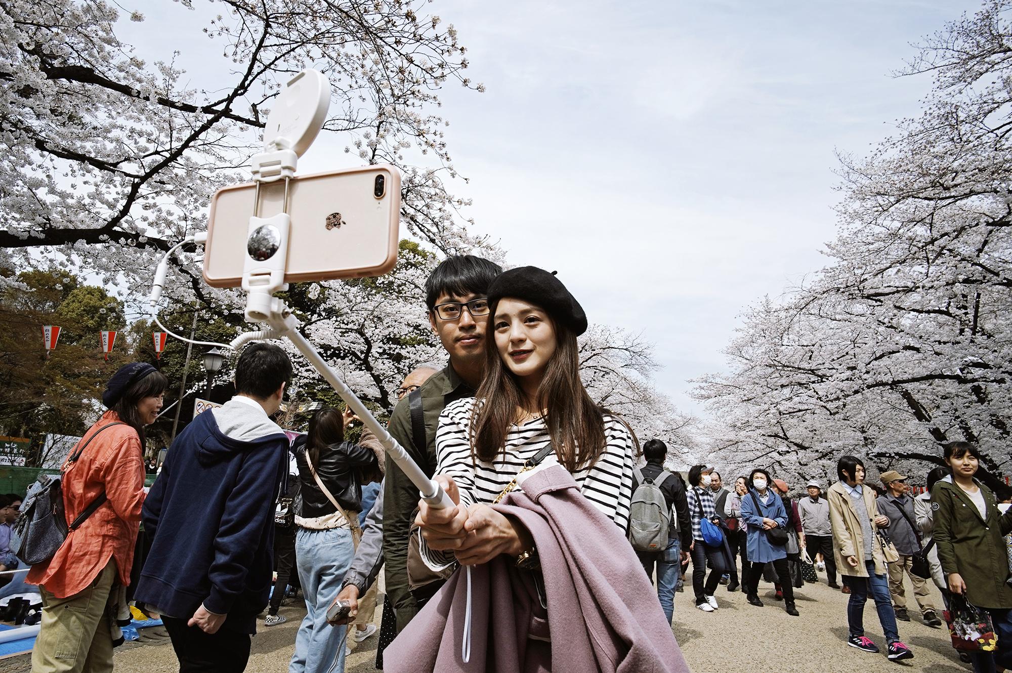 Пара делает селфи впарке Уэно, Токио