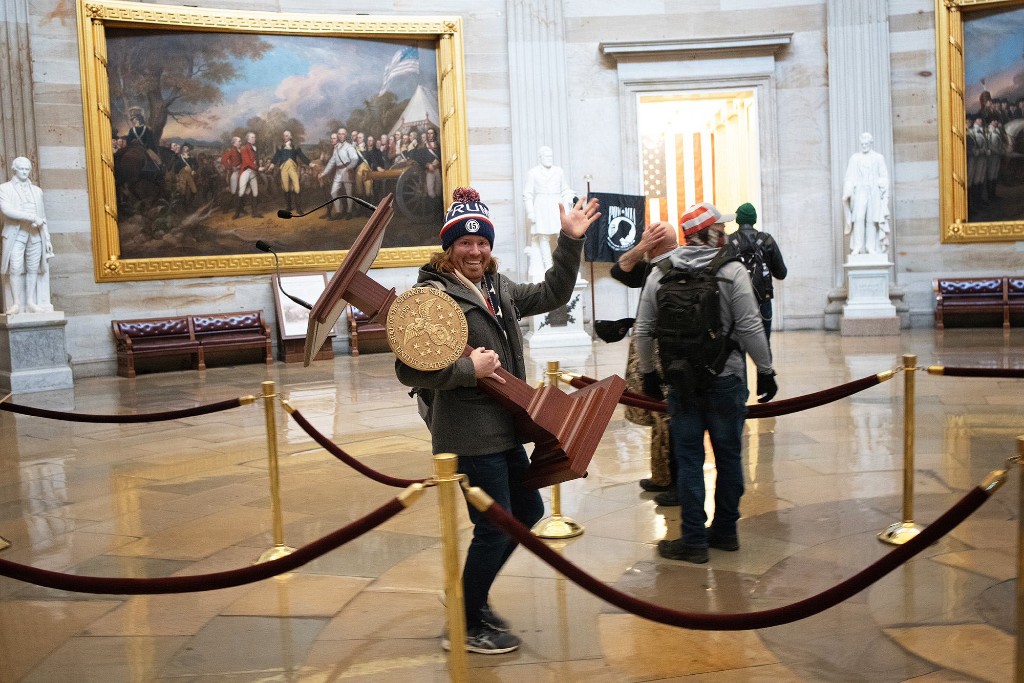A pro-Trump protester carries the lectern of U.S. Speaker of the House Nancy Pelosi through the Roturnda of the U.S. Capitol Building after a pro-Trump mob stormed the building on January 06, 2021 in Washington, DC. Congress held a joint session today to ratify President-elect Joe Biden's 306-232 Electoral College win over President Donald Trump. A group of Republican senators said they would reject the Electoral College votes of several states unless Congress appointed a commission to audit the election results. (Photo by Win McNamee/Getty Images)