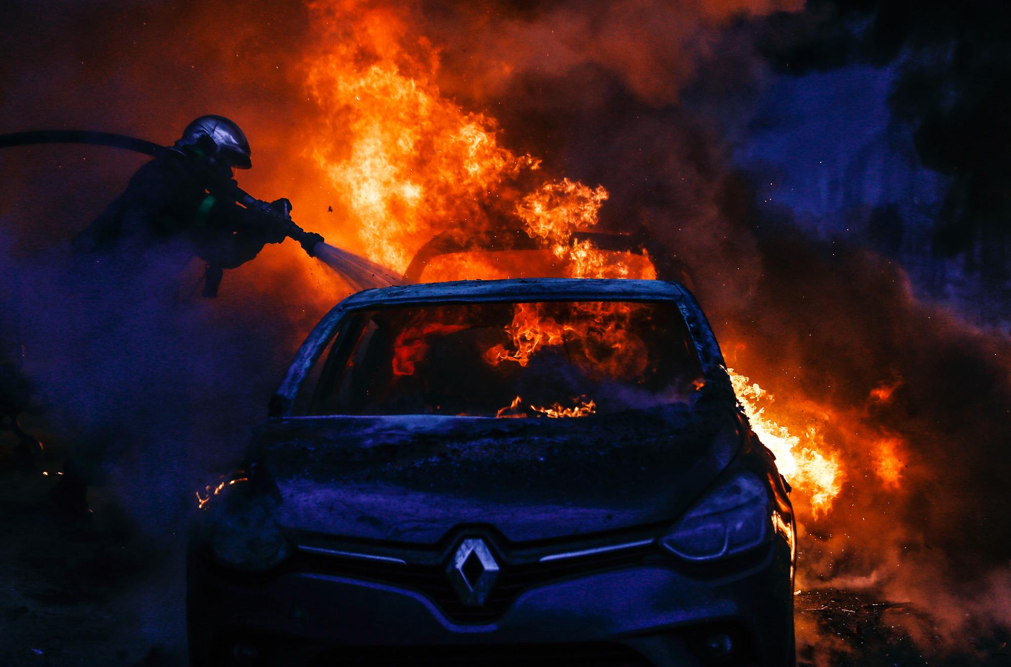 Пожарные тушат автомобиль, загоревшийся врезультате столкновения «желтых жилетов» ссиловиками около Триумфальной арки