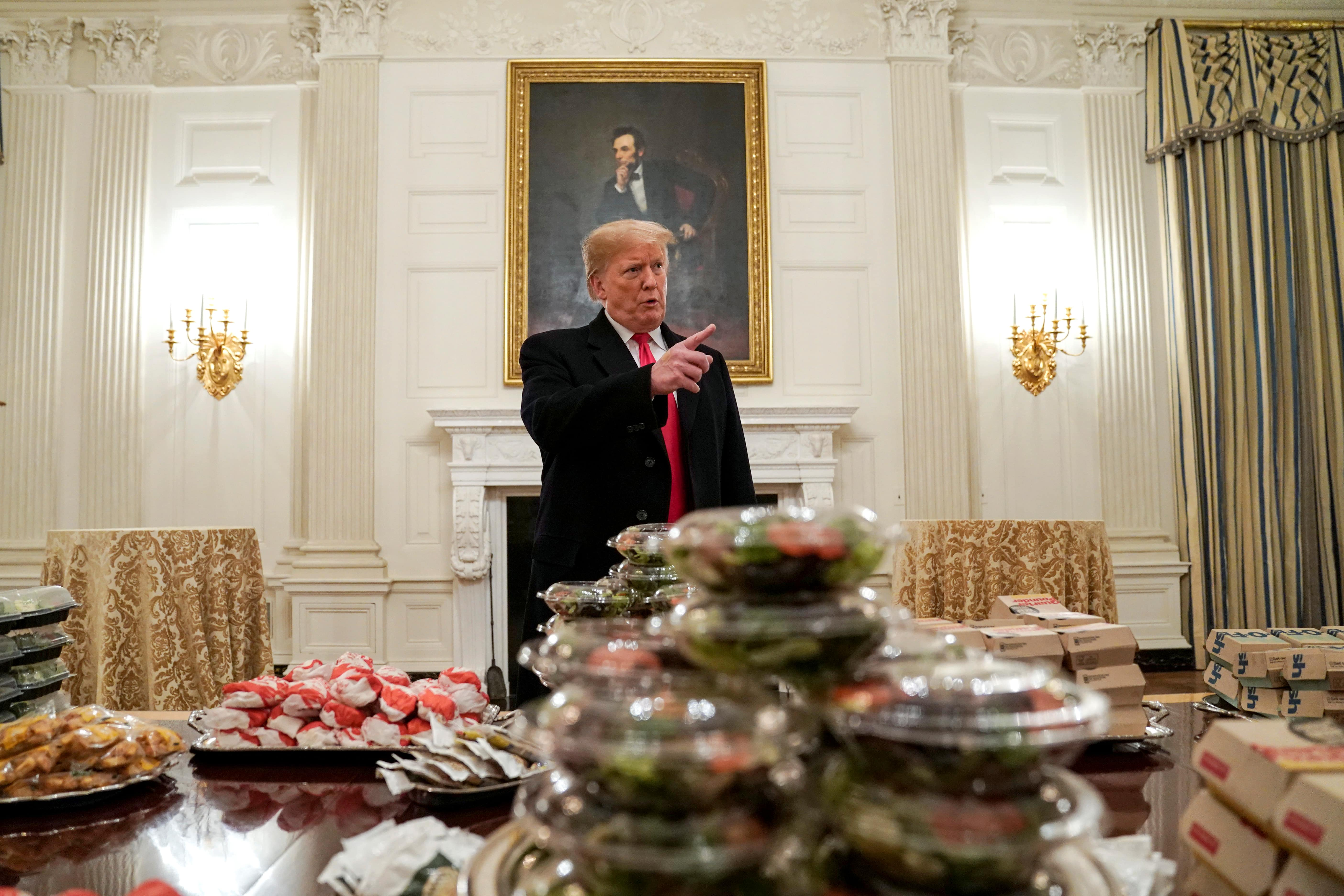 U.S. President Donald Trump speaks in front of fast food provided for the 2018 College Football Playoff National Champion Clemson Tigers due to the partial government shutdown in the State Dining Room of the White House in Washington, U.S., January 14, 2019. REUTERS/Joshua Roberts T