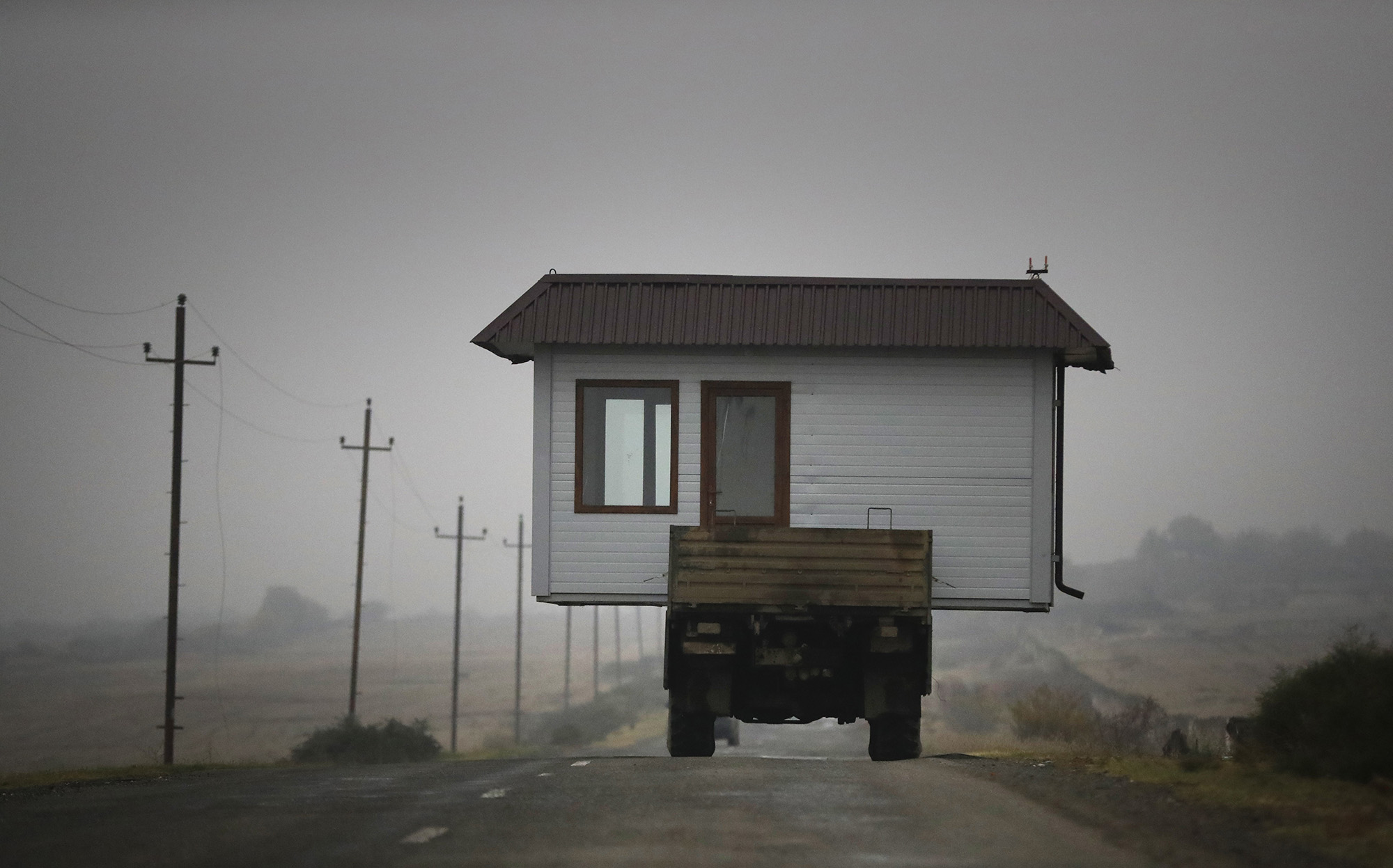 A family drives a truck loaded with a small house along a highway as they leave their home village in the separatist region of Nagorno-Karabakh, Wednesday, Nov. 18, 2020. A Russia-brokered cease-fire to halt six weeks of fighting over Nagorno-Karabakh stipulated that Armenia turn over control of some areas it holds outside the separatist territory's borders to Azerbaijan. Armenians are forced to leave their homes before the region is handed over to control by Azerbaijani forces. (AP Photo/Sergei Grits