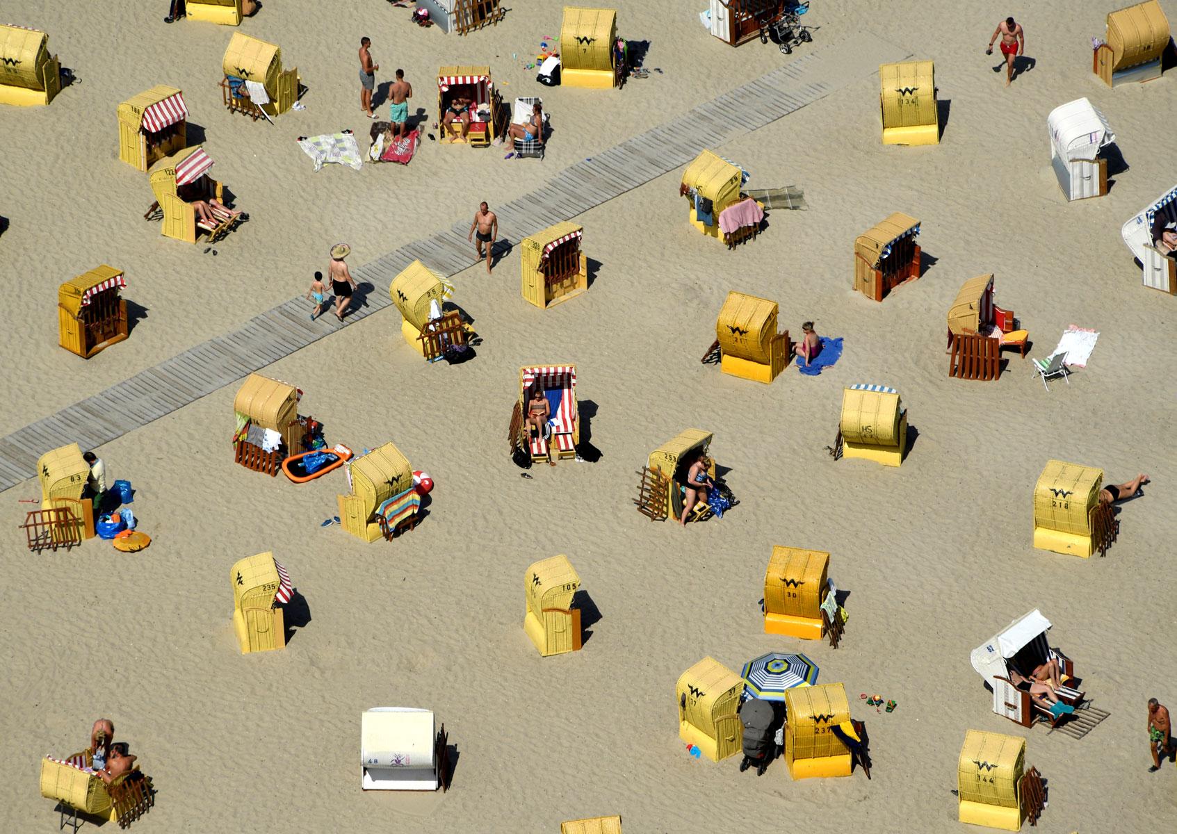 Люди загорают напляже наберегу Балтийского моря вТравемюнде, Германия