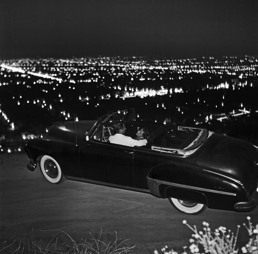A couple in their car on Mulholland Drive overlooking the city at night on June 7 1951 in Los Angeles California. (Photo by Earl Leaf/Michael Ochs Archive/Getty Images)